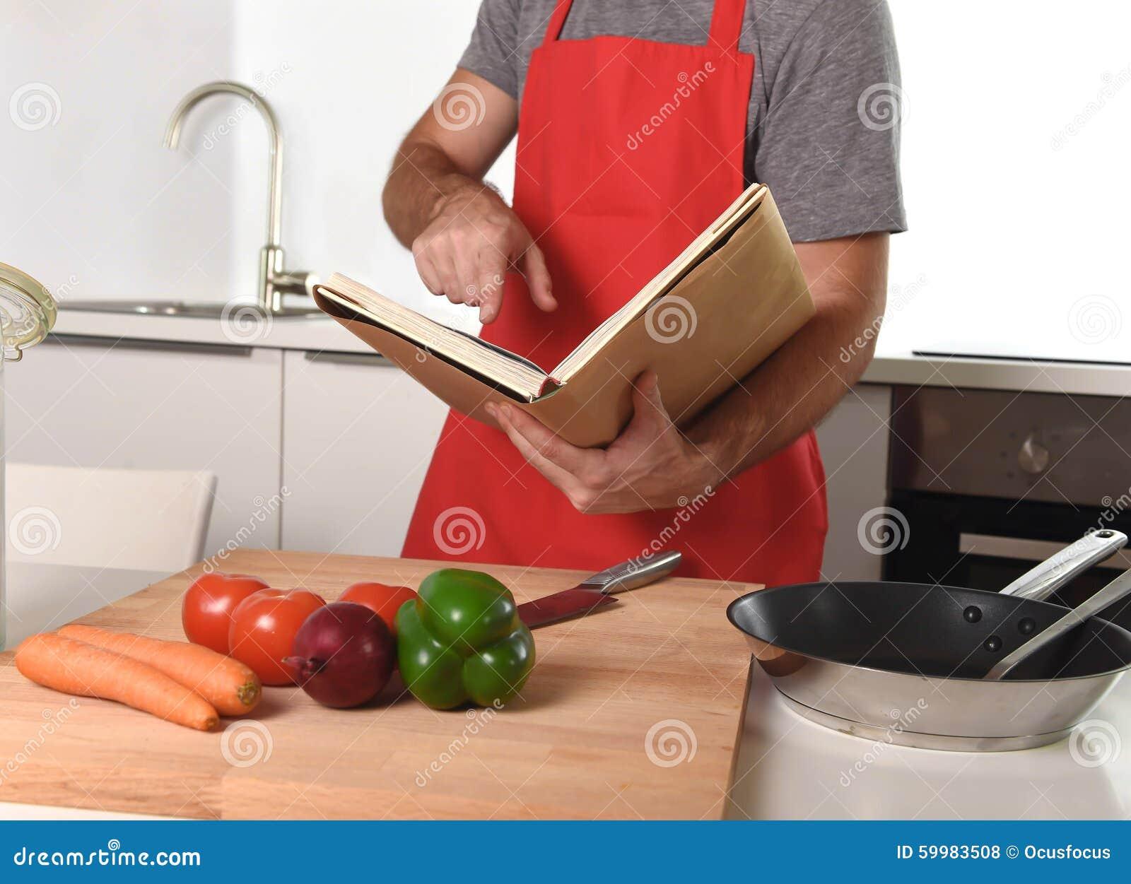 Uomo irriconoscibile in grembiule alla cucina dopo la cottura sana del libro di ricetta