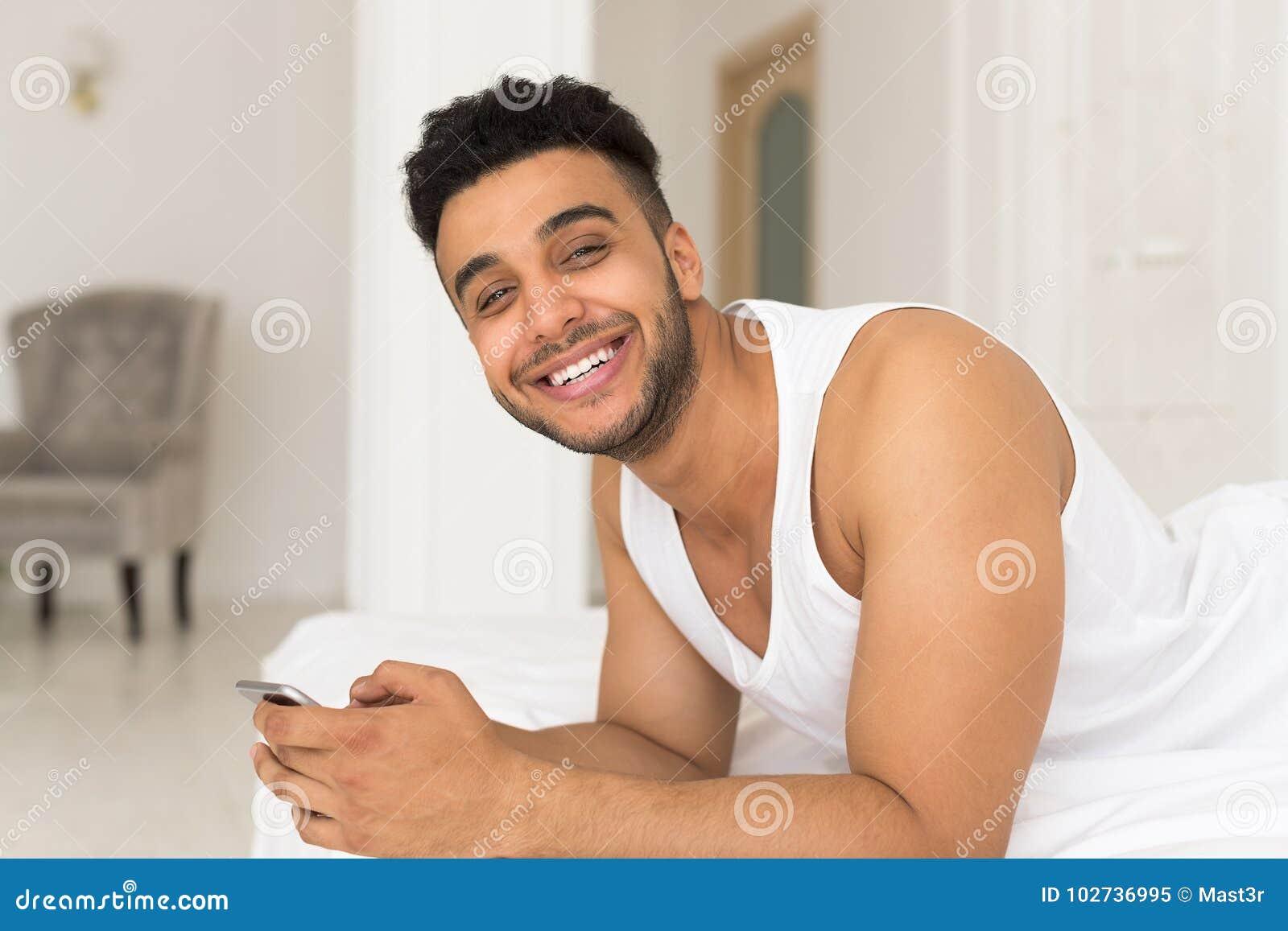 Uomo ispano bello che si trova a letto facendo uso dello - Uomo leone a letto ...