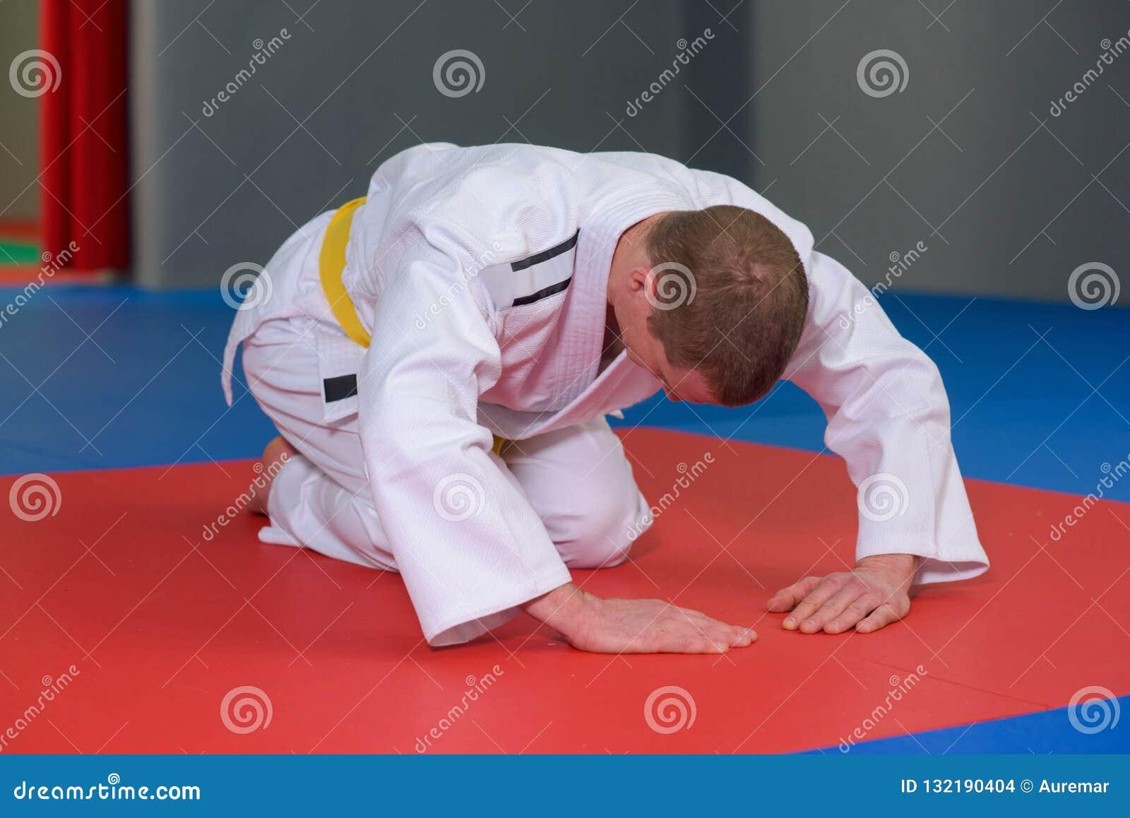 Uomo in kimono nella posizione piegata sul pavimento