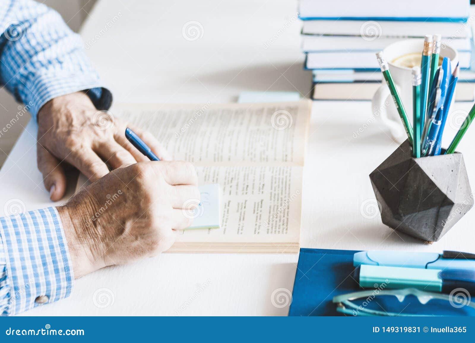 Uomo in libro di lettura blu della camicia sul posto di lavoro alla moda moderno con gli articoli per ufficio e libri, concetto d