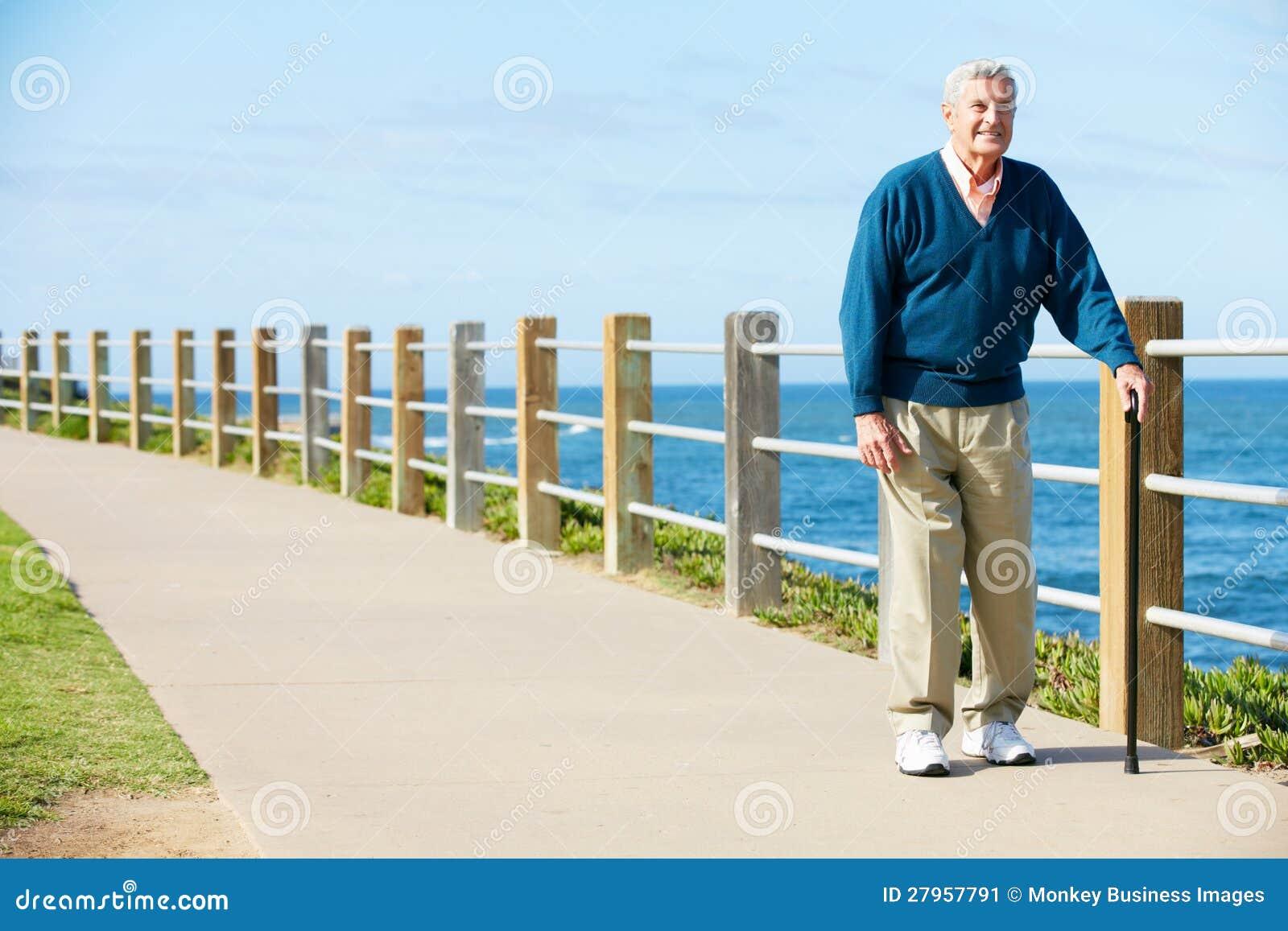 Uomo maggiore che cammina lungo il percorso dal mare