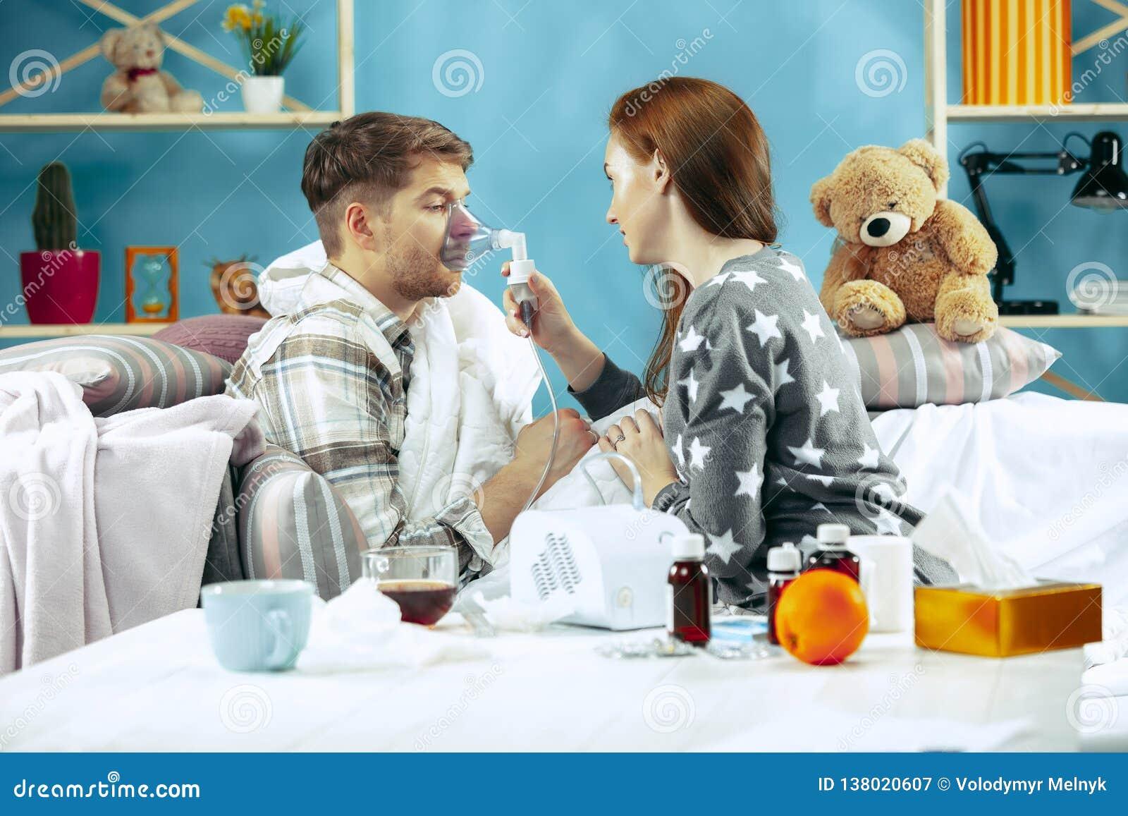 Uomo malato barbuto con il condotto di scarico che si siede sul sofà a casa Malattia, influenza, concetto di dolore Rilassamento