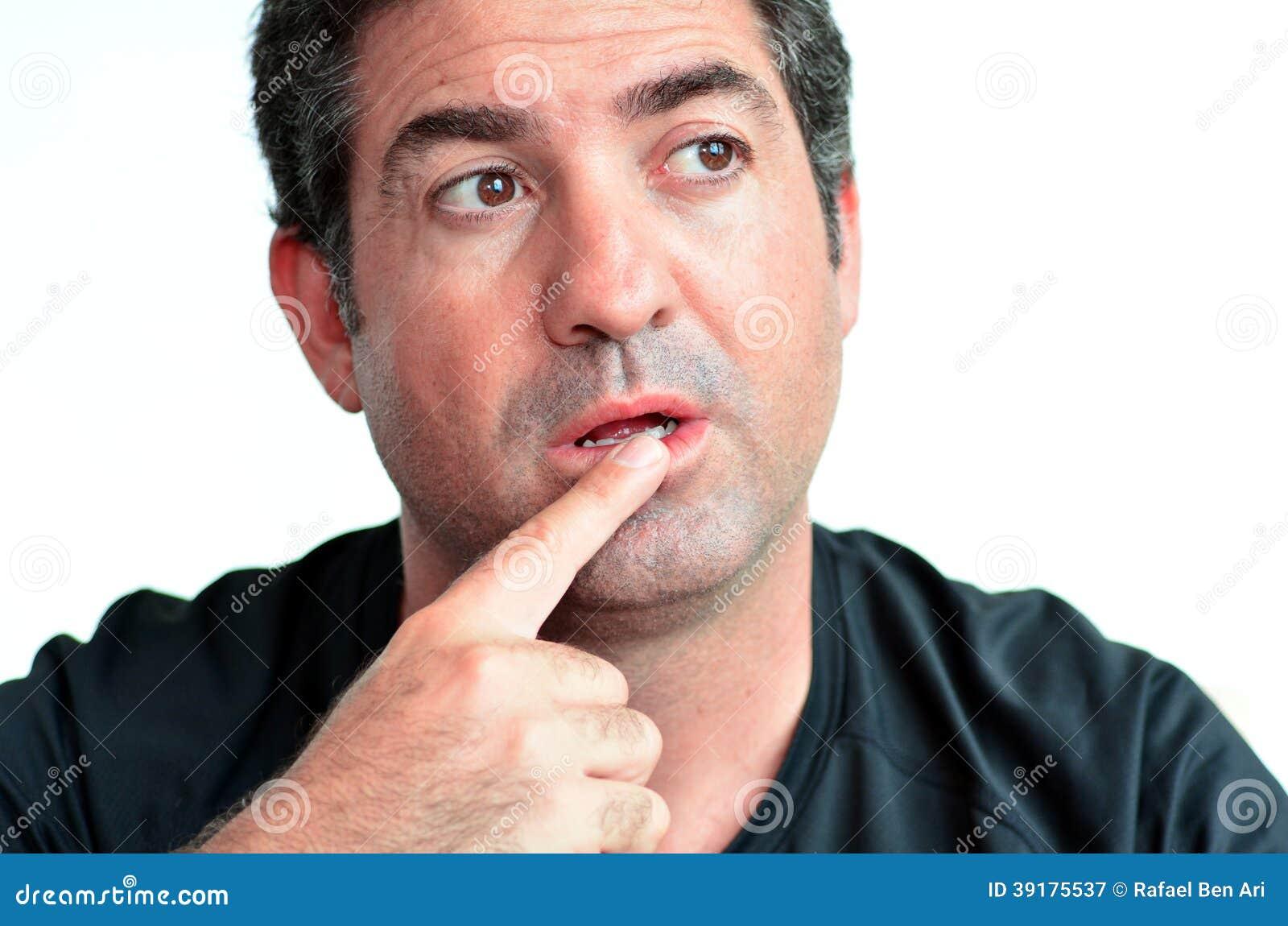 Uomo maturo che pensa con un dito sulle sue labbra