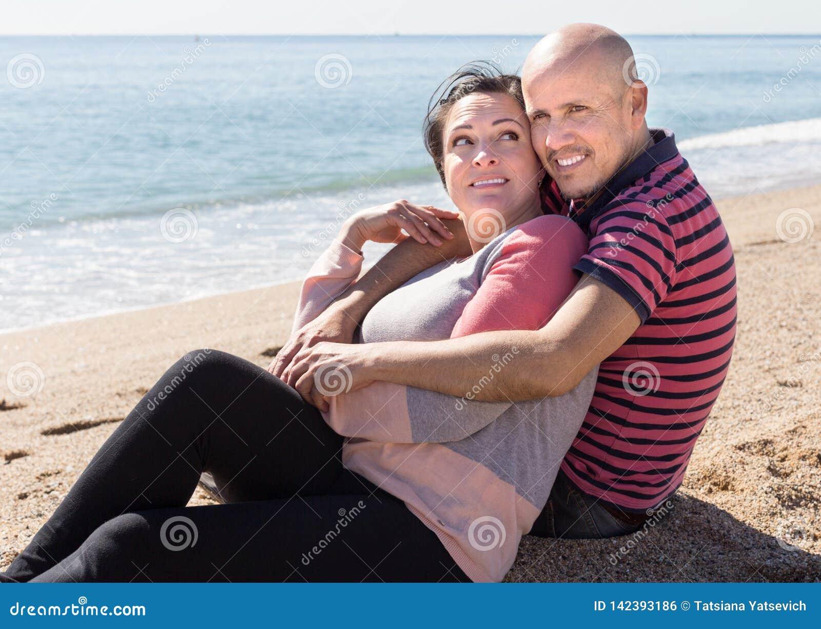 Uomo maturo e femmina che si siedono vicino al mare