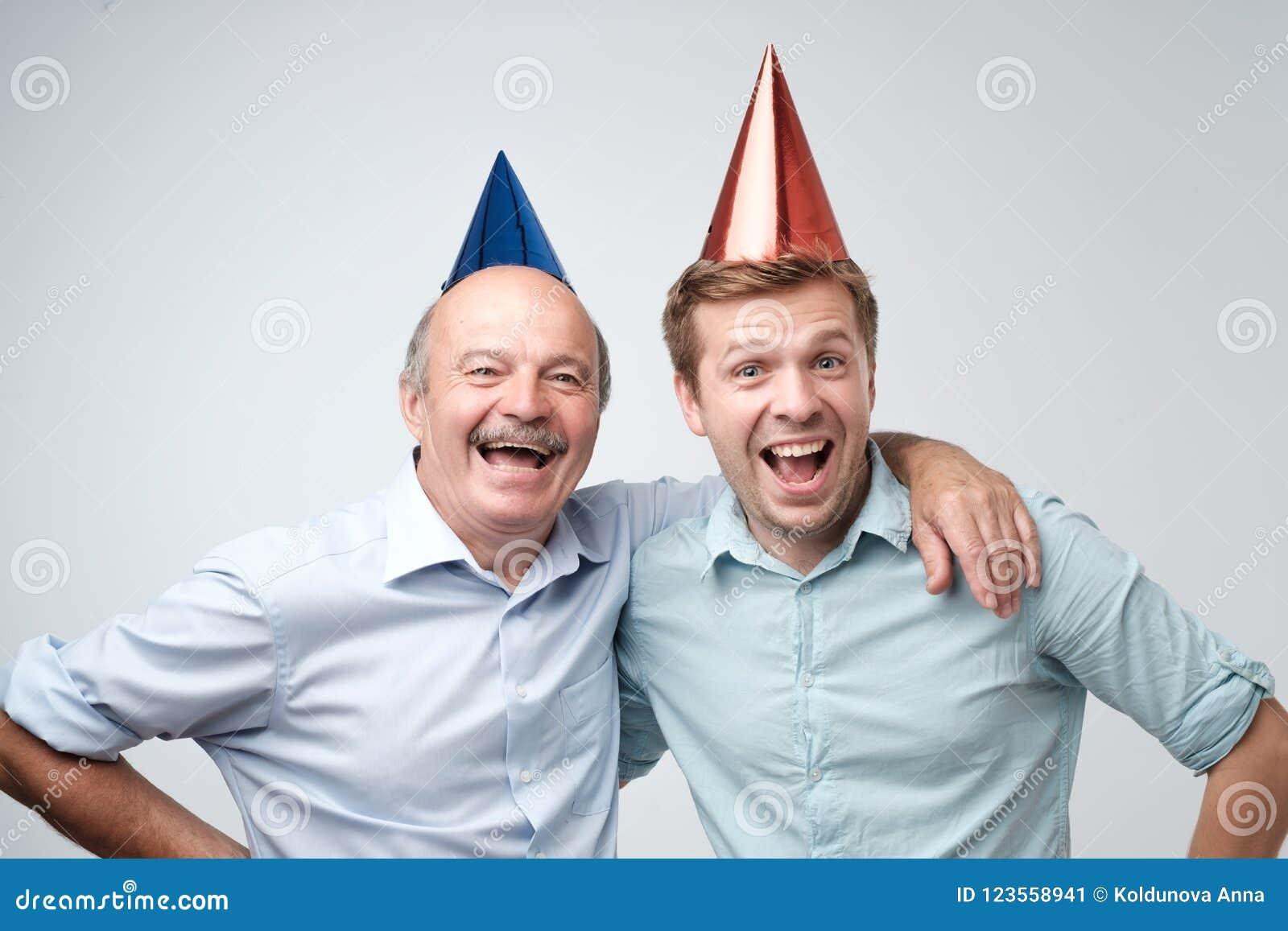 Uomo maturo e suo giovane il figlio che celebrano buon compleanno che indossa i cappucci divertenti