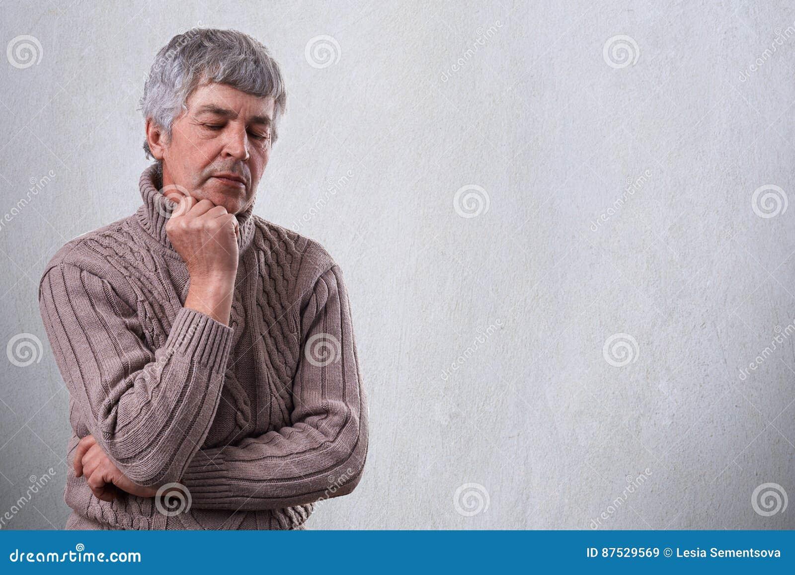 Uomo maturo triste pensieroso che tiene la sua mano sotto il suo mento che guarda giù con l espressione infelice che pensa a qual