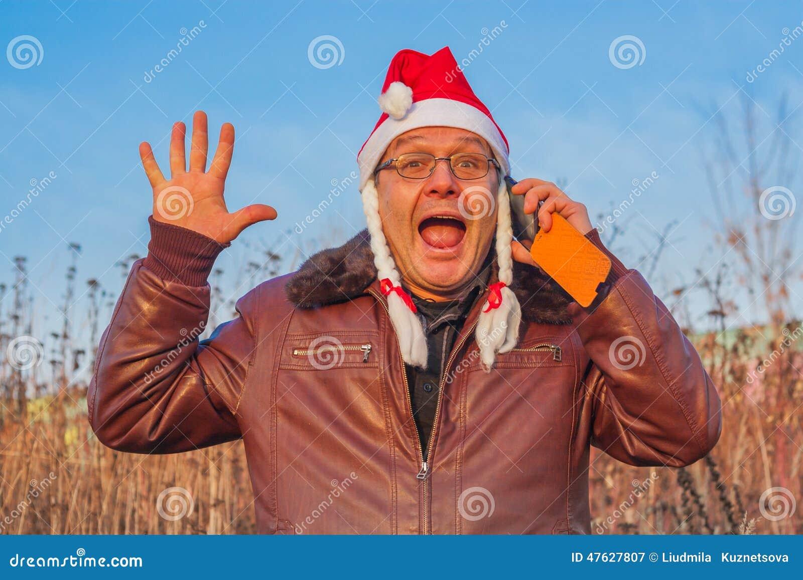 Uomo molto emozionale in cappello divertente di Santa che parla sul telefono