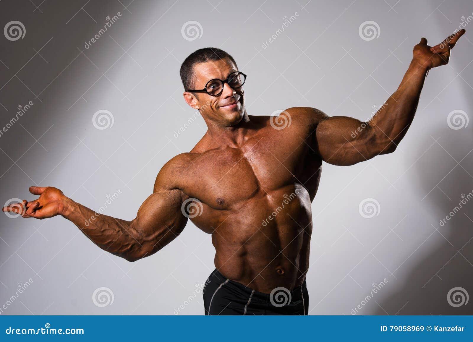 Uomo muscolare felice con un torso nudo ed i vetri divertenti