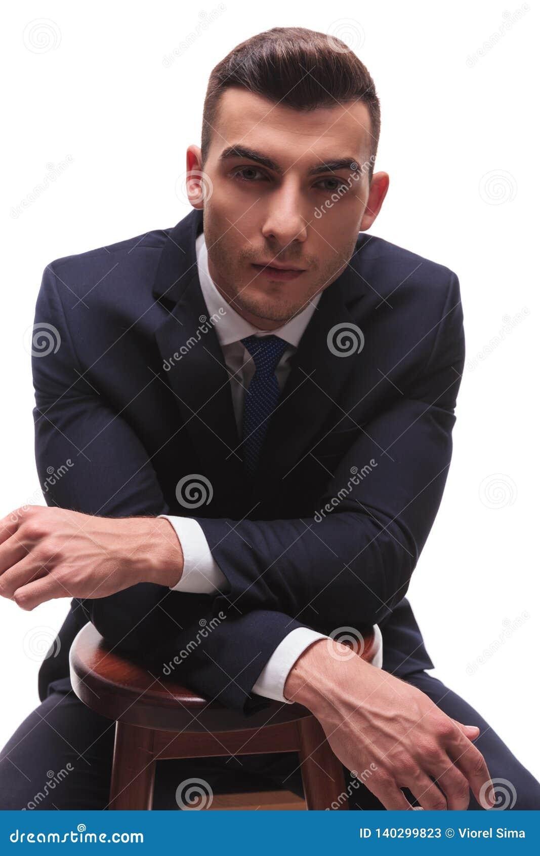 Uomo muscoloso in vestito con le mani di riposo attraversate