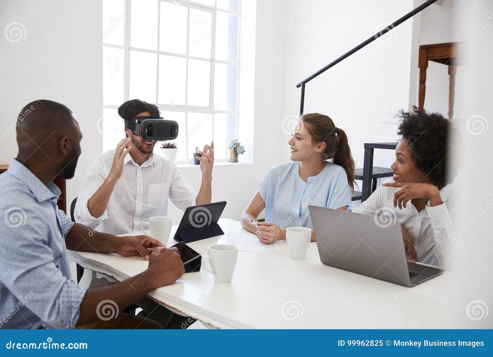 Uomo negli occhiali di protezione di VR ad uno scrittorio guardato dai colleghi in ufficio