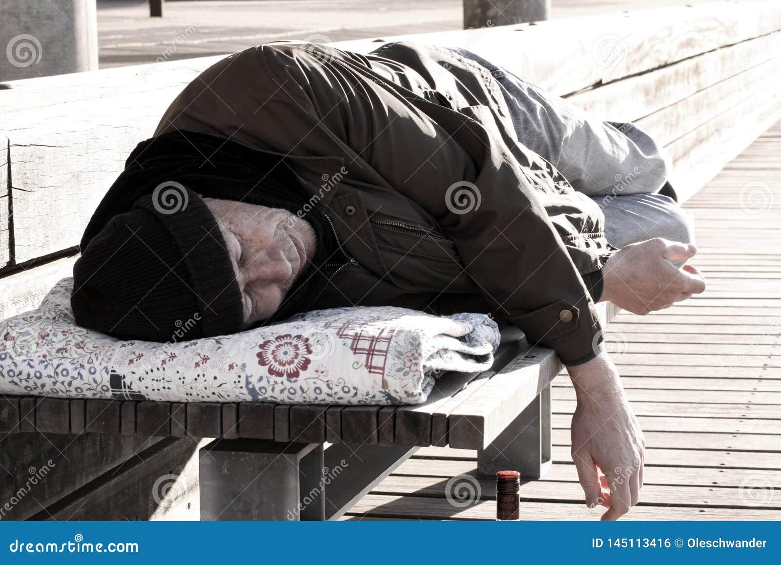Uomo o rifugiato senza tetto che dorme sul banco di legno con la bottiglia