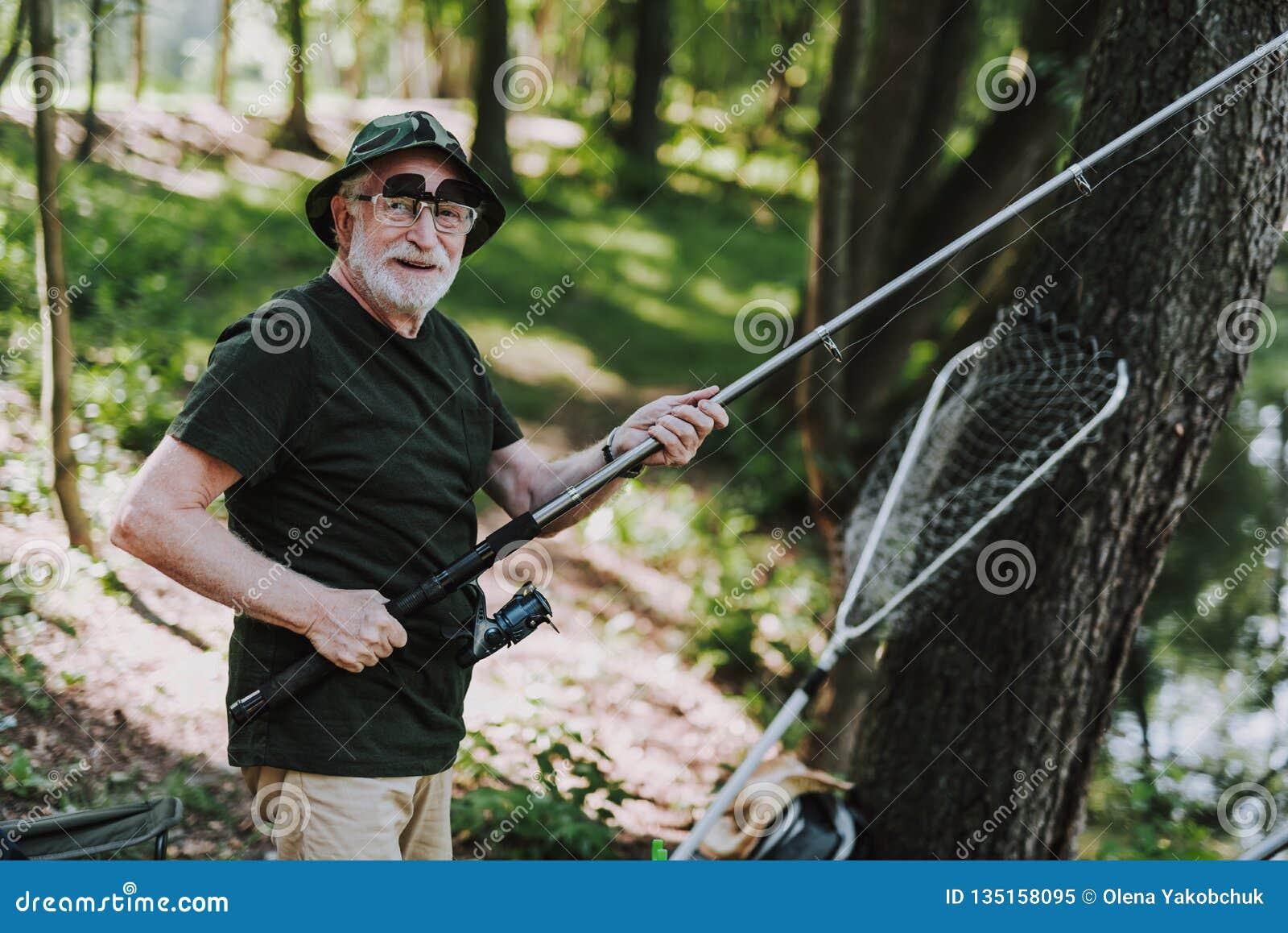 Uomo pensionato allegro che gode dell attività di pesca con piacere
