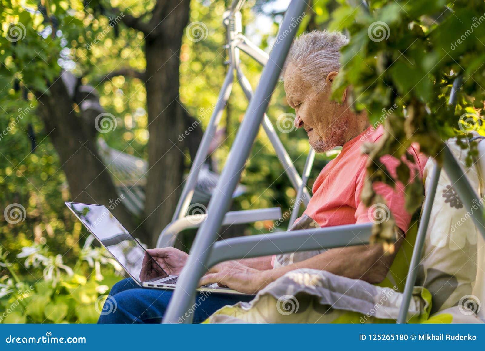 Uomo pensionato anziano che lavora al computer nel giardino del cottage di estate