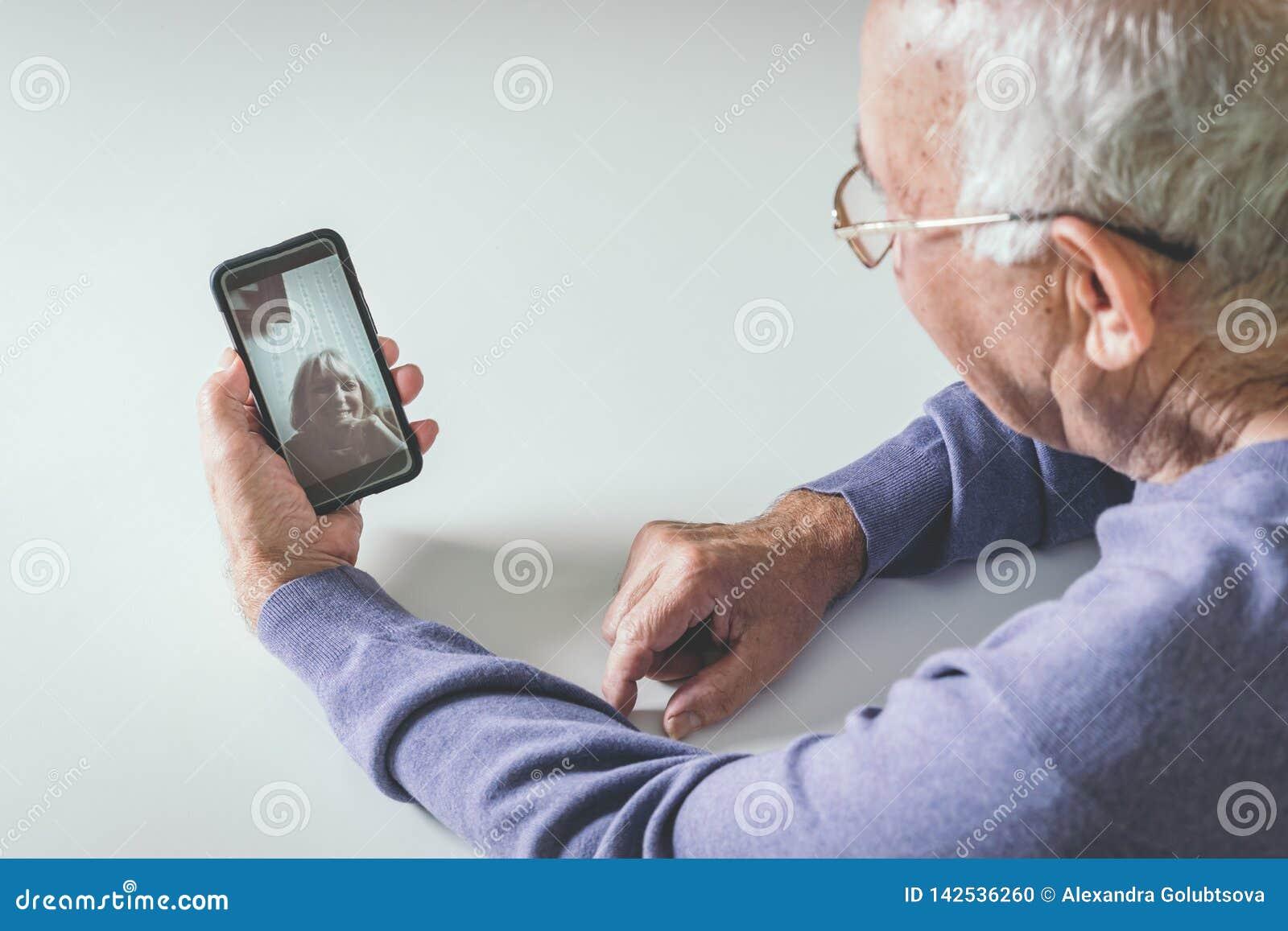 Uomo pensionato facendo uso delle tecnologie informatiche a casa