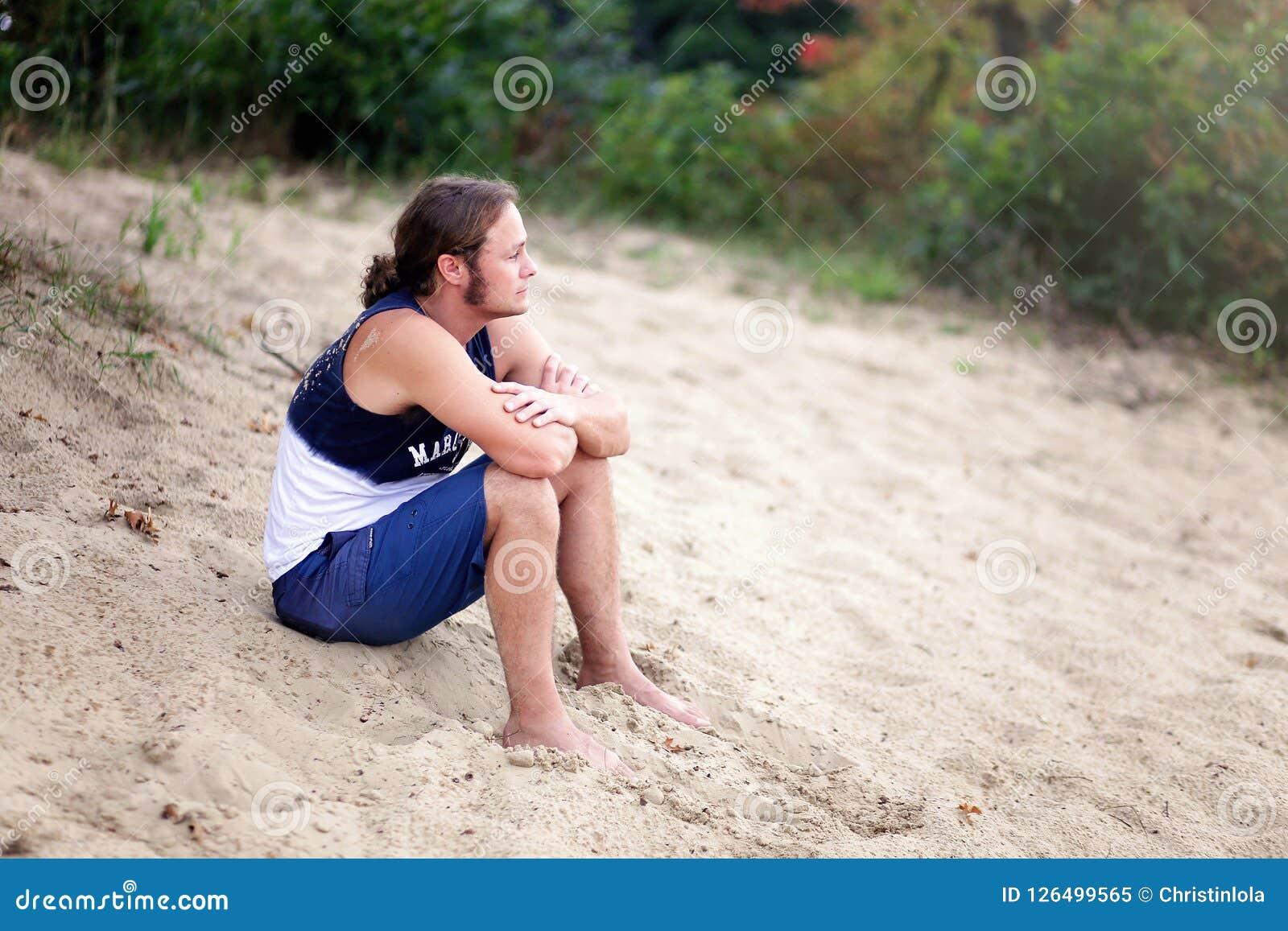 Uomo scalzo dai capelli lunghi che si siede sulla spiaggia che guarda fuori sopra la t