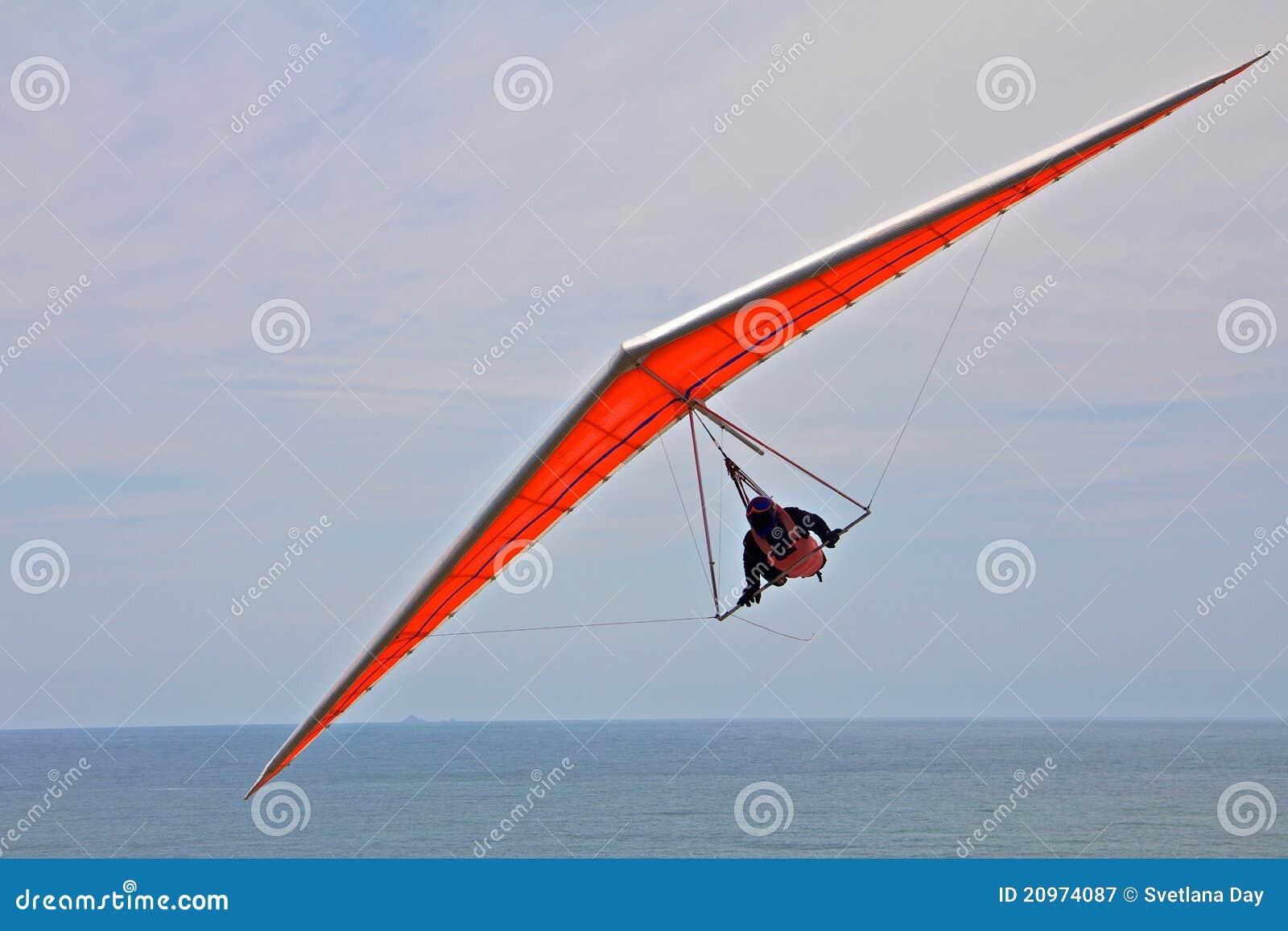 Uomo scivolare di caduta su un ala arancione nel cielo