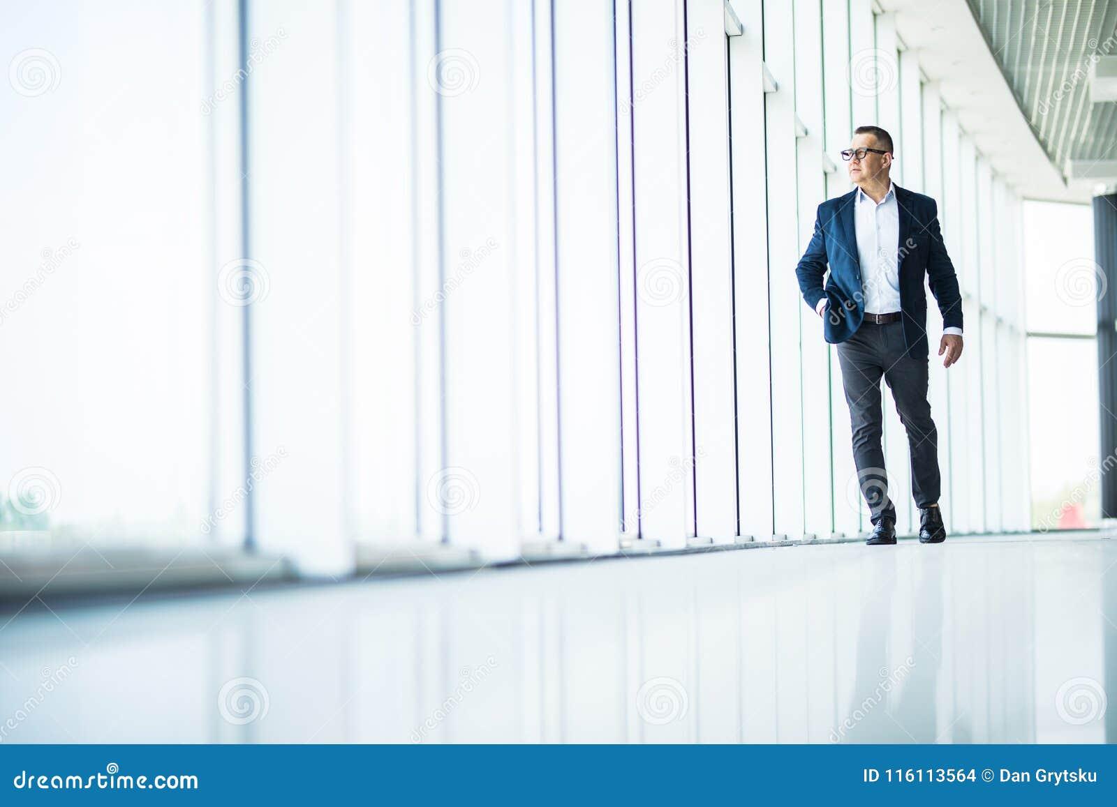 Uomo senior bello e riuscito di affari che cammina nell interno moderno dell ufficio