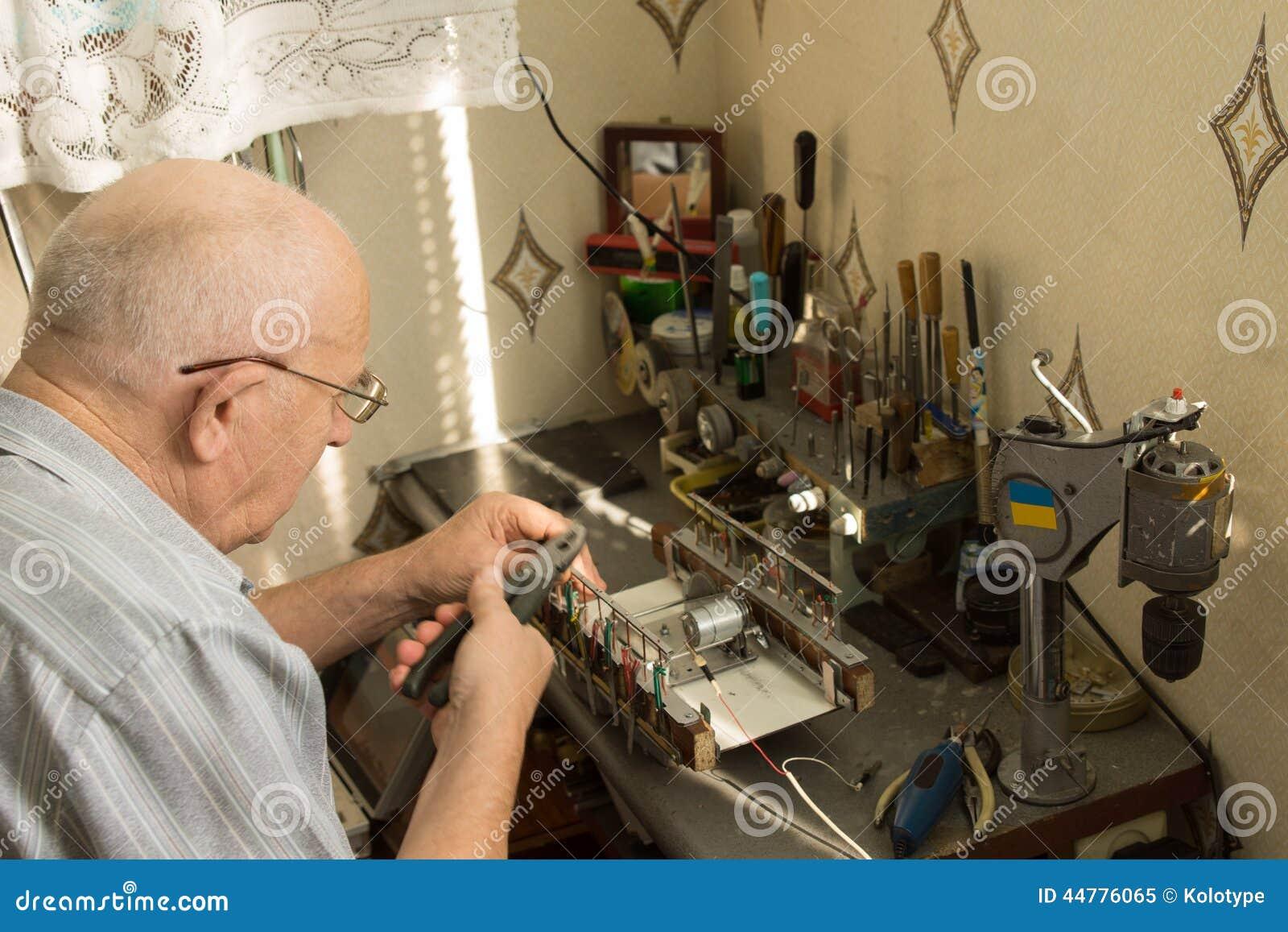 Uomo Senior Che Lavora Ad Un Piccolo Banco Da Lavoro Fotografia ...