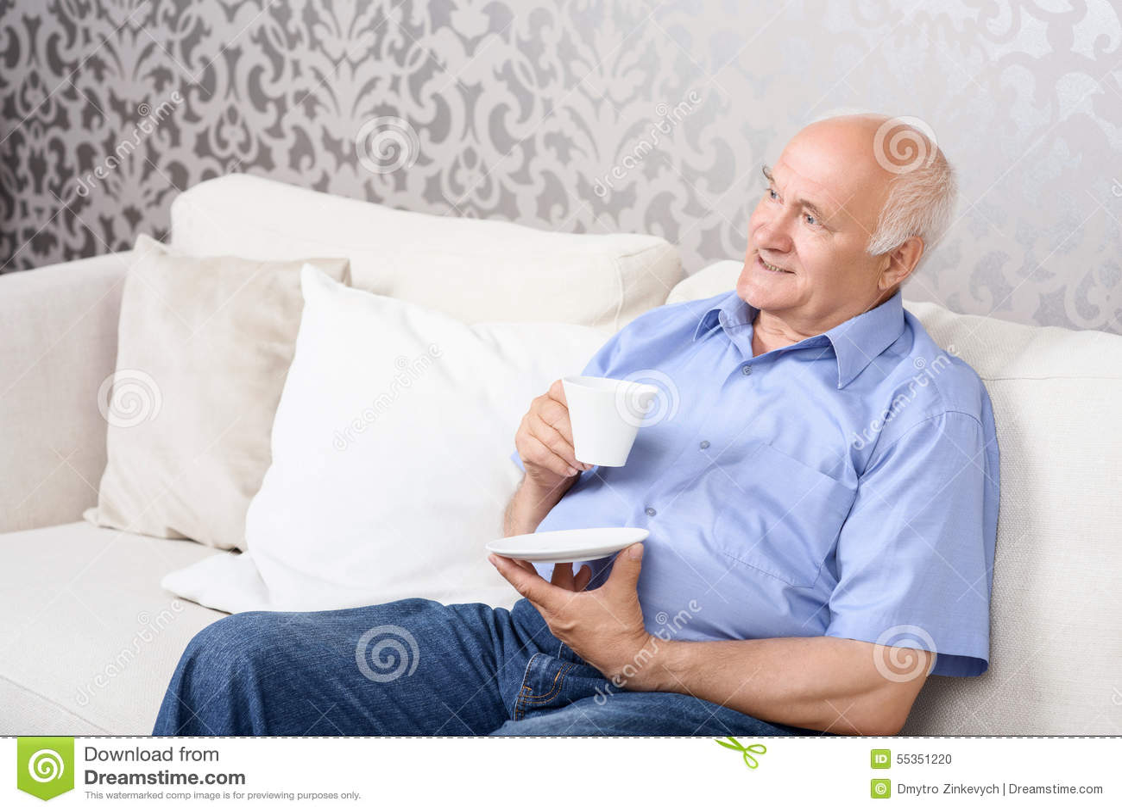 Uomo senior che si siede sullo strato con la tazza