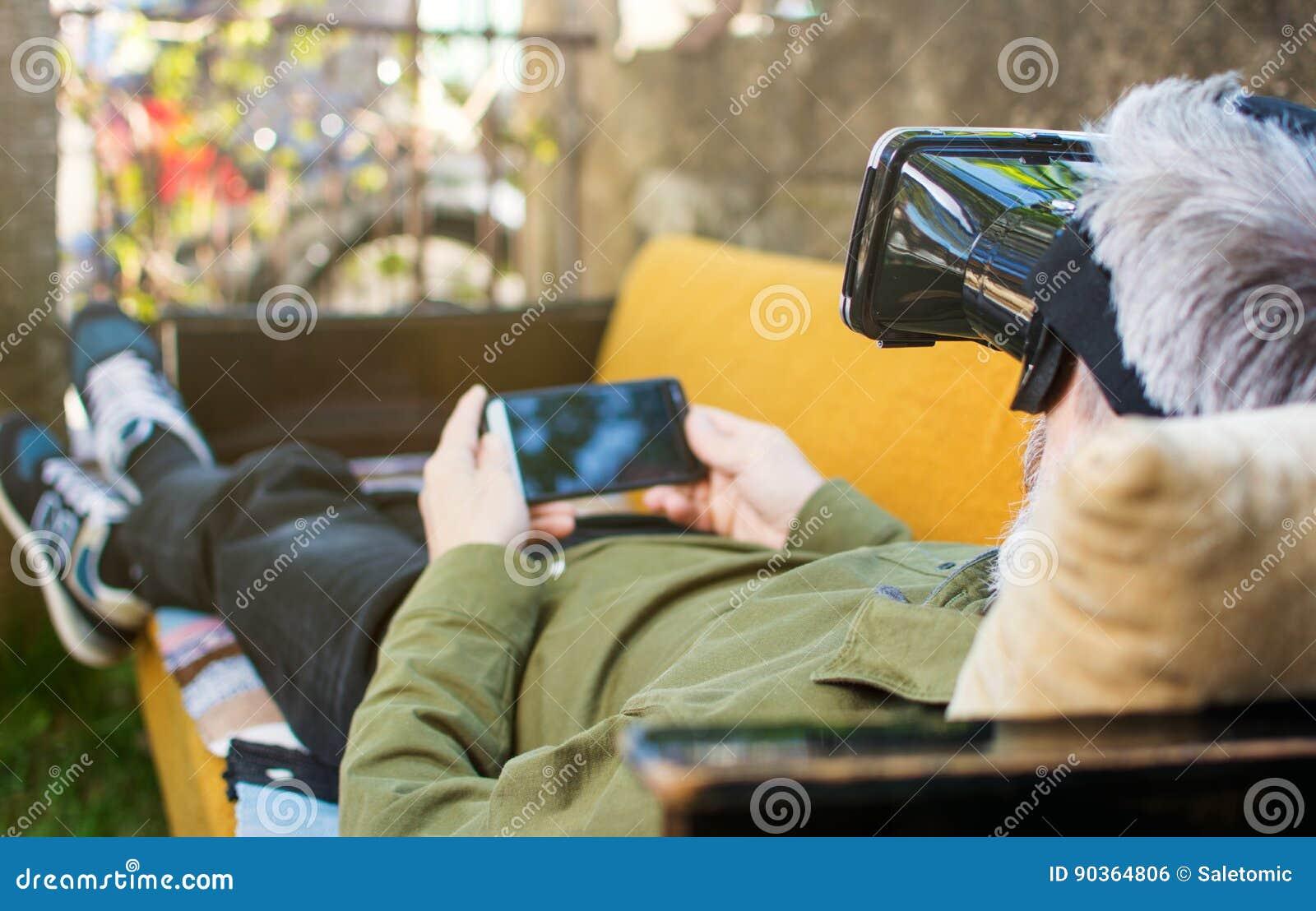 Uomo senior che usando realtà virtuale su un letto di sofà