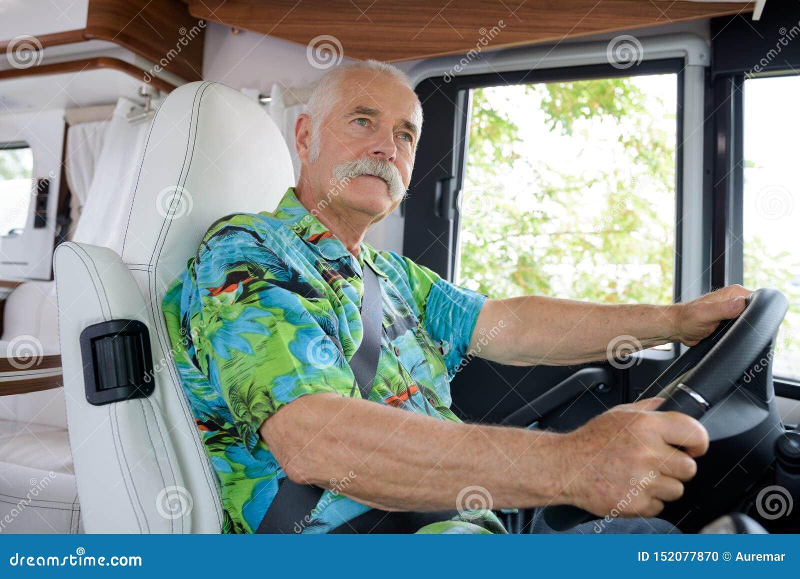 Uomo senior del ritratto che conduce furgone