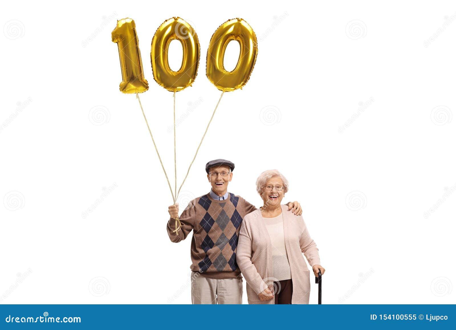 Uomo senior e donna con un pallone dorato di numero cento