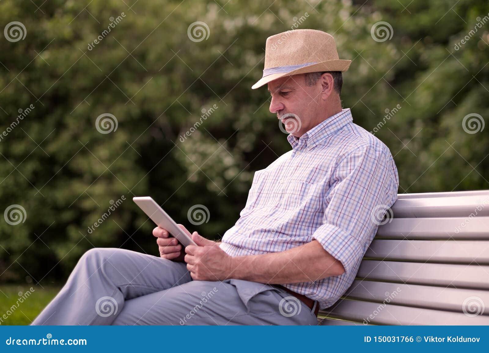 Uomo senior ispano in compressa della lettura del cappello di estate nello spazio della copia del parco