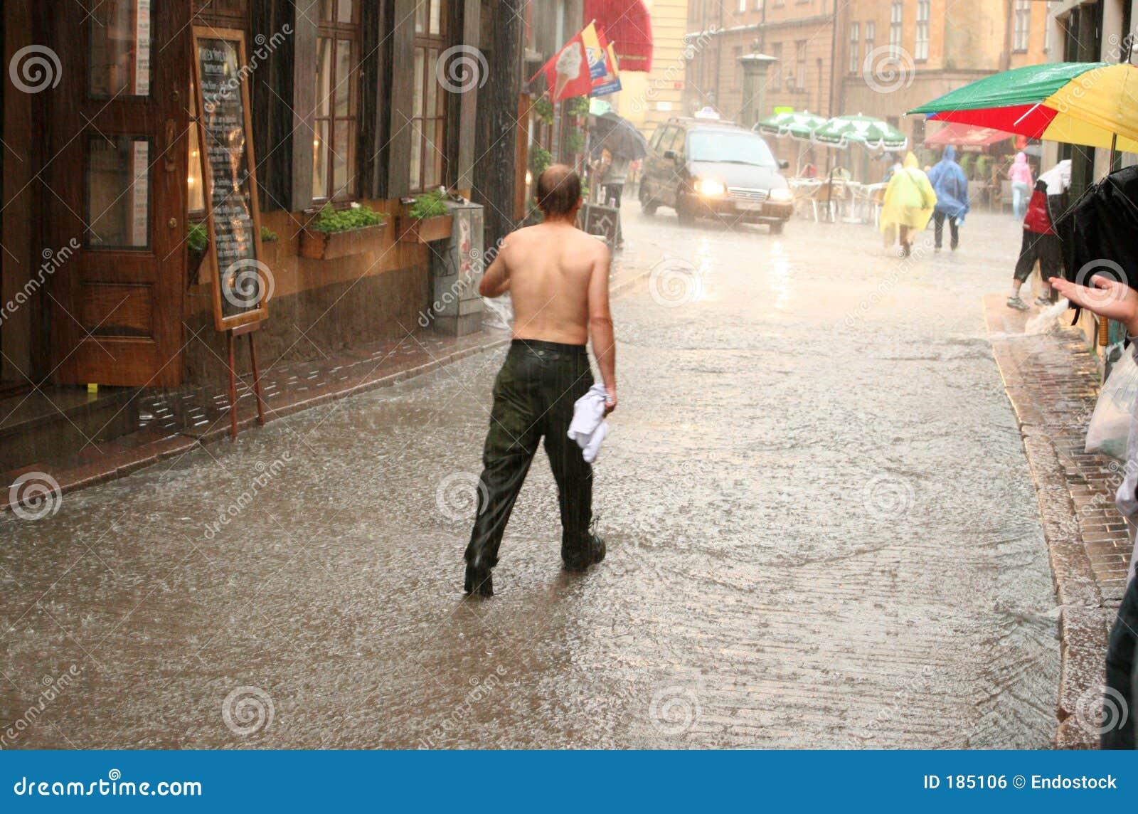 Uomo senza camicia che cammina nella pioggia
