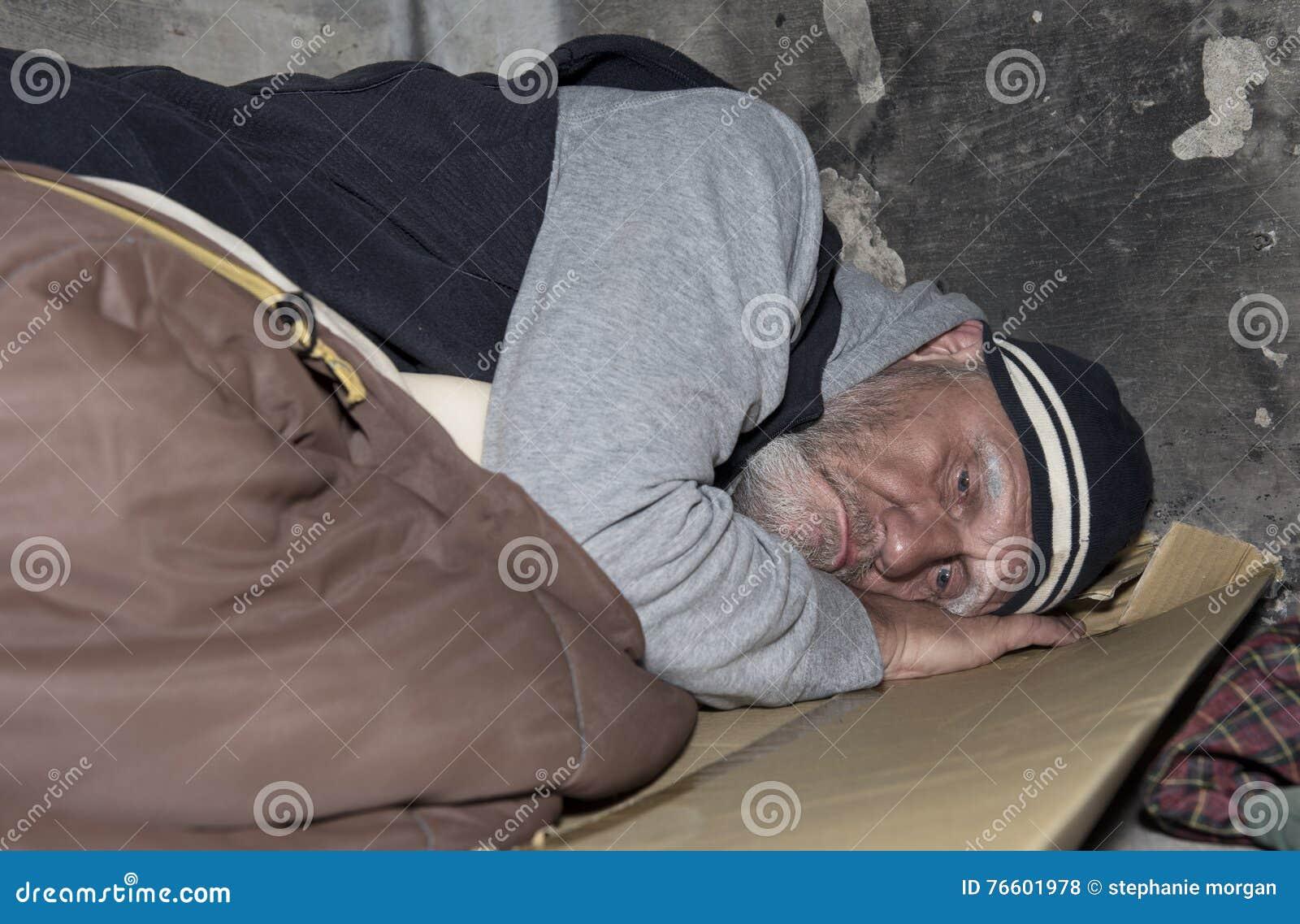 Uomo senza tetto che dorme sul cartone e su un vecchio sacco a pelo o