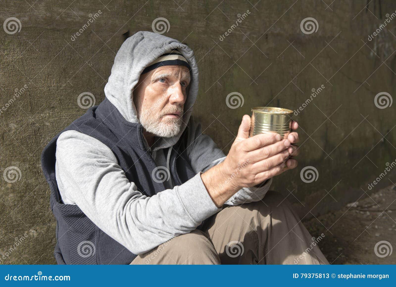 Uomo senza tetto maturo che sembra alimentato su, tenendo un barattolo di latta vuoto