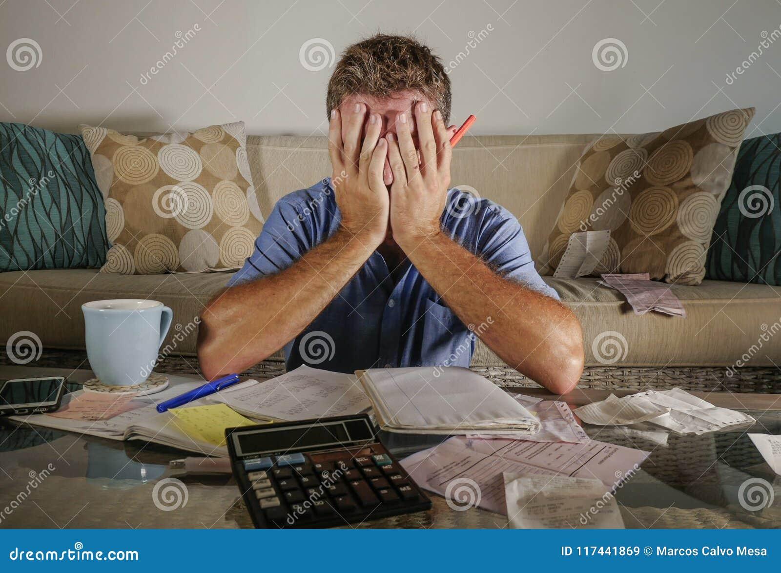 Uomo sollecitato preoccupato attraente a casa che calcola le spese di imposta di mese con i pagamenti di contabilità del calcolat