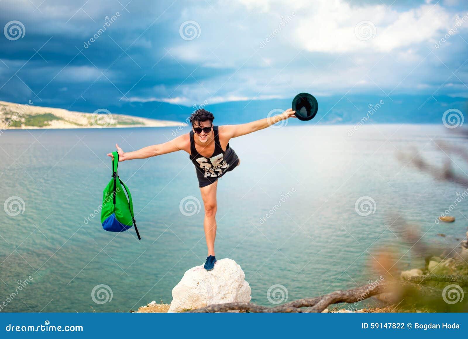 Uomo sopra la scogliera, sulla linea costiera della spiaggia