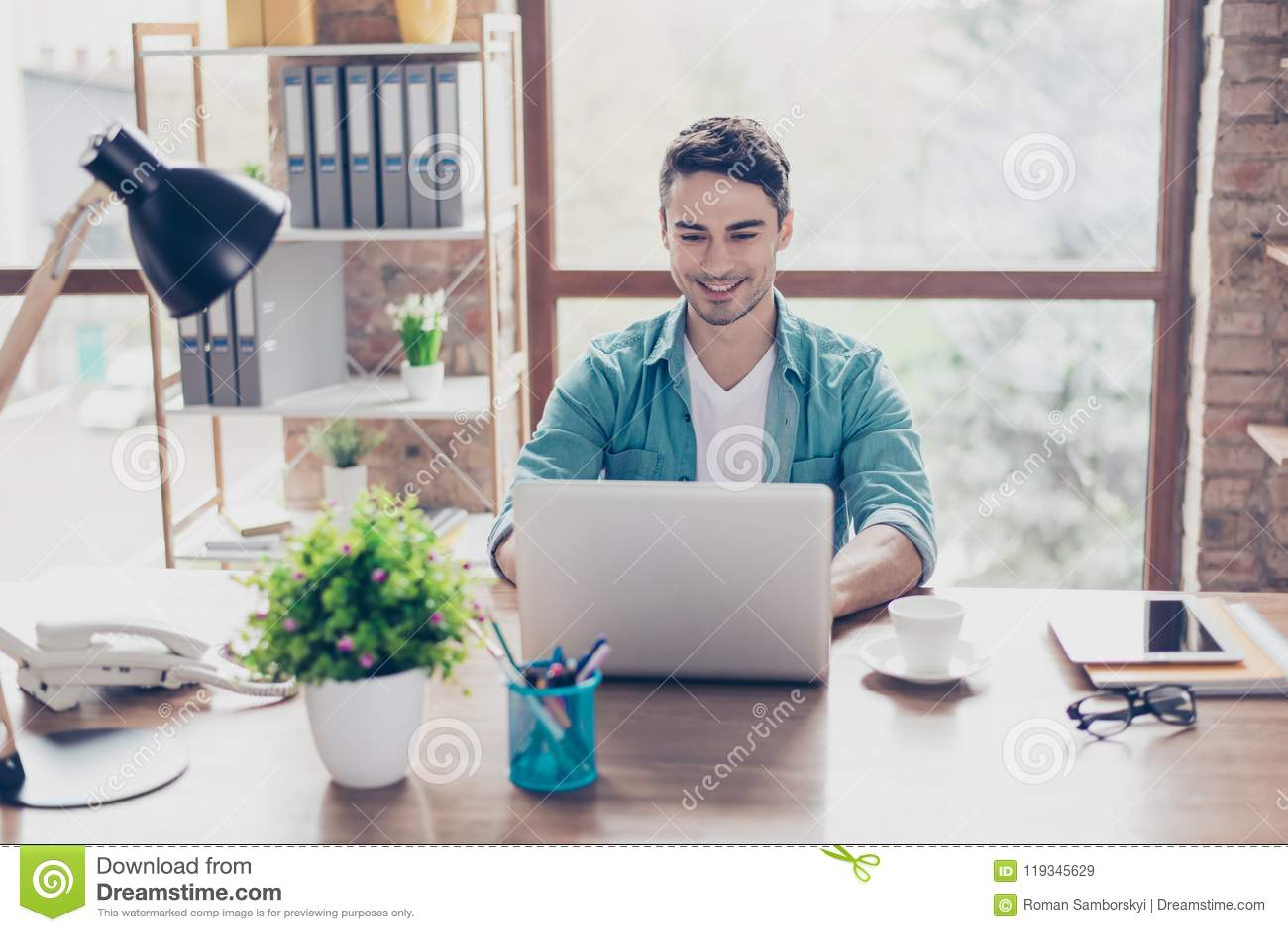 Uomo sorridente bello felice che si siede alla tavola ed allo spirito di chiacchierata