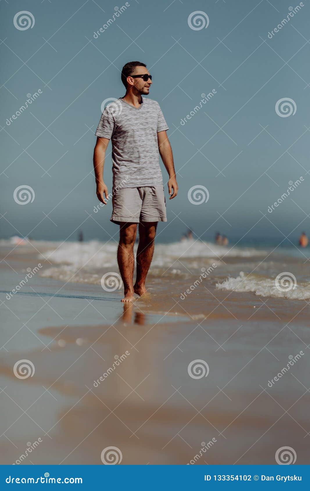 Uomo sorridente bello in occhiali da sole che cammina e che gode del giorno sulla spiaggia