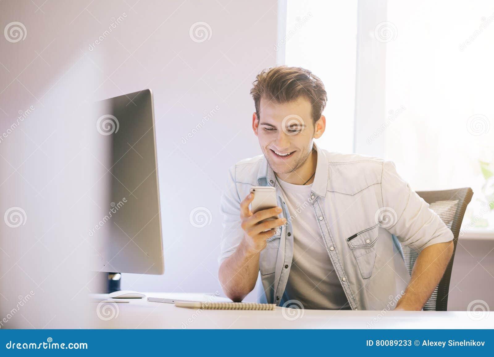 Uomo sorridente che comunica sul telefono mobile mentre utilizzando computer portatile allo scrittorio nello studio