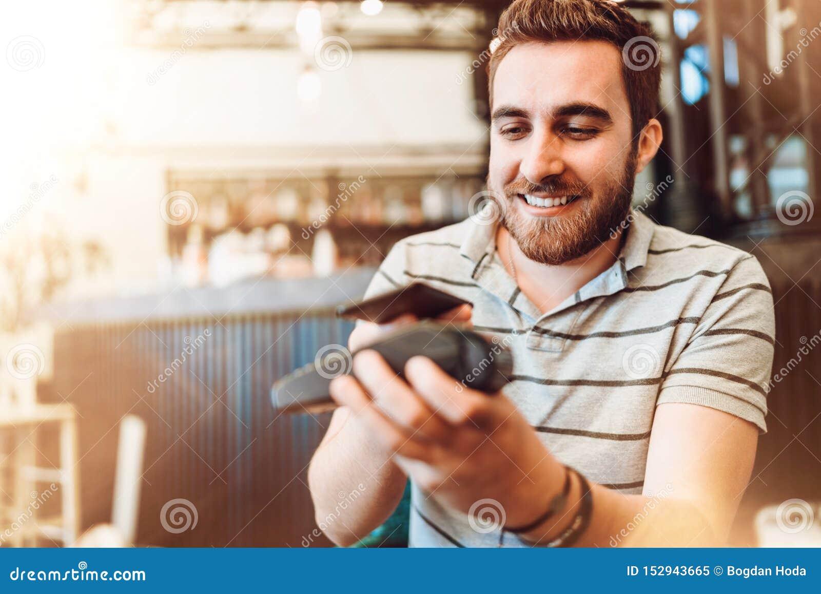 Uomo sorridente che effettua un pagamento senza fili, cliente che per mezzo del telefono cellulare, dispositivo con tecnologia de