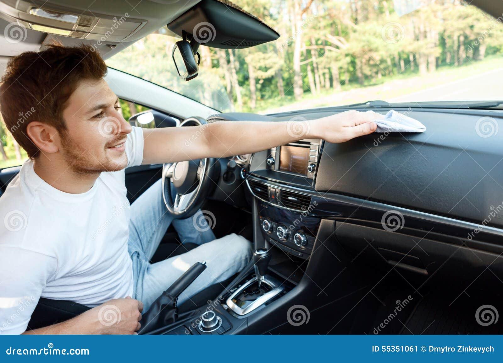 Uomo sorridente che pulisce polvere dentro l automobile