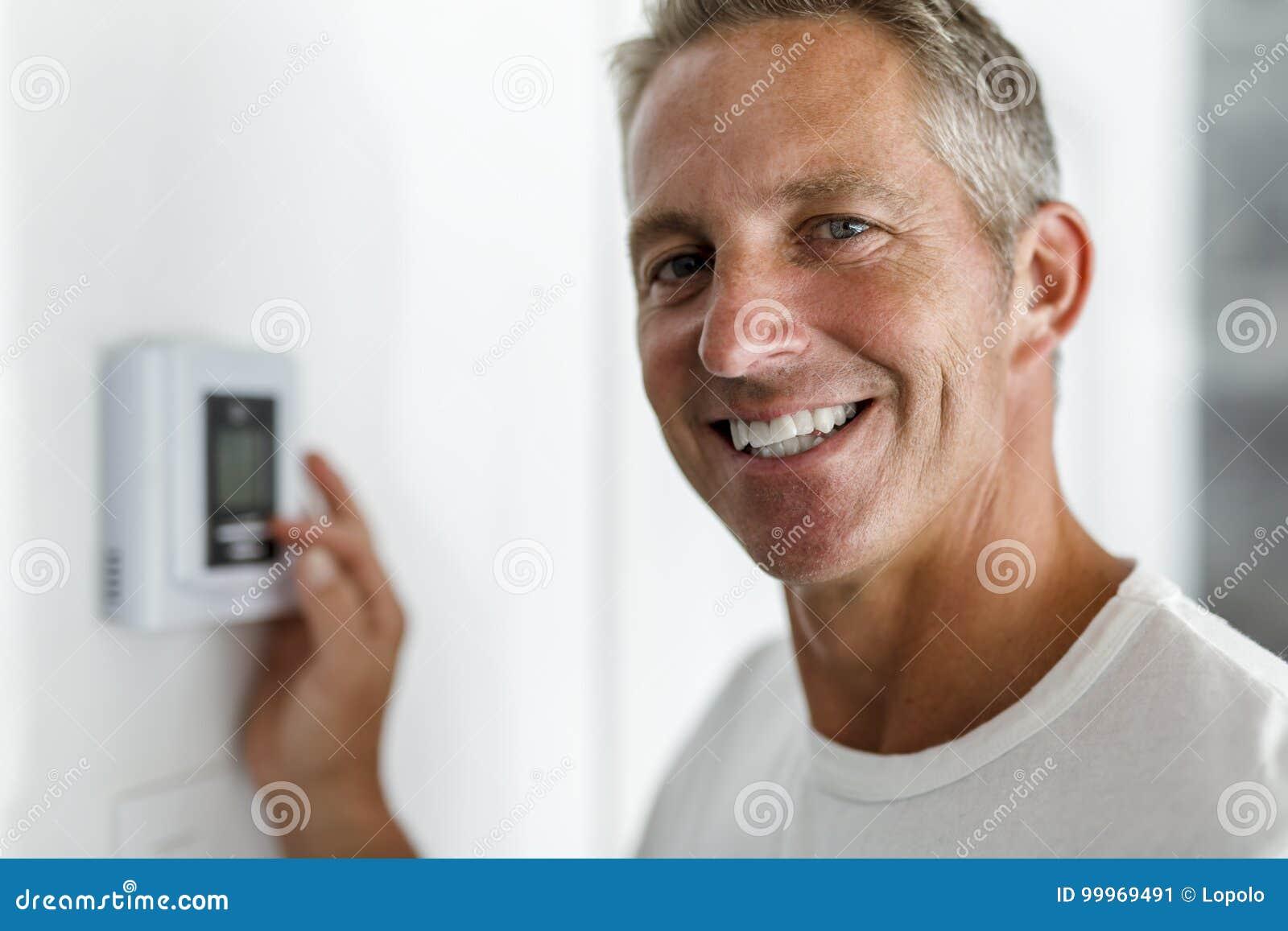 Uomo sorridente che regola termostato sul sistema del riscaldamento domestico