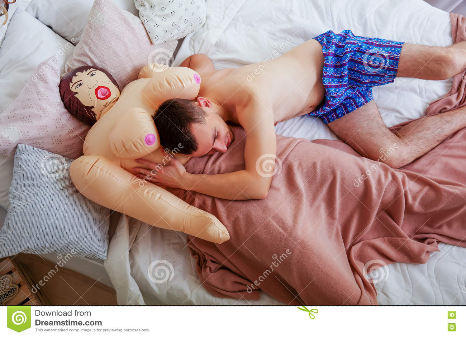 Foto A Letto.Uomo Sorridente Che Si Trova A Letto Con La Bambola Di Gomma