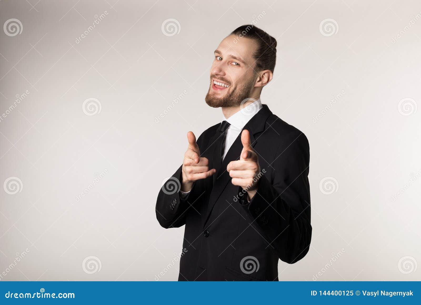 Uomo sorridente felice con la barba e l acconciatura d avanguardia che indossano vestito nero che esamina e che indica la macchin