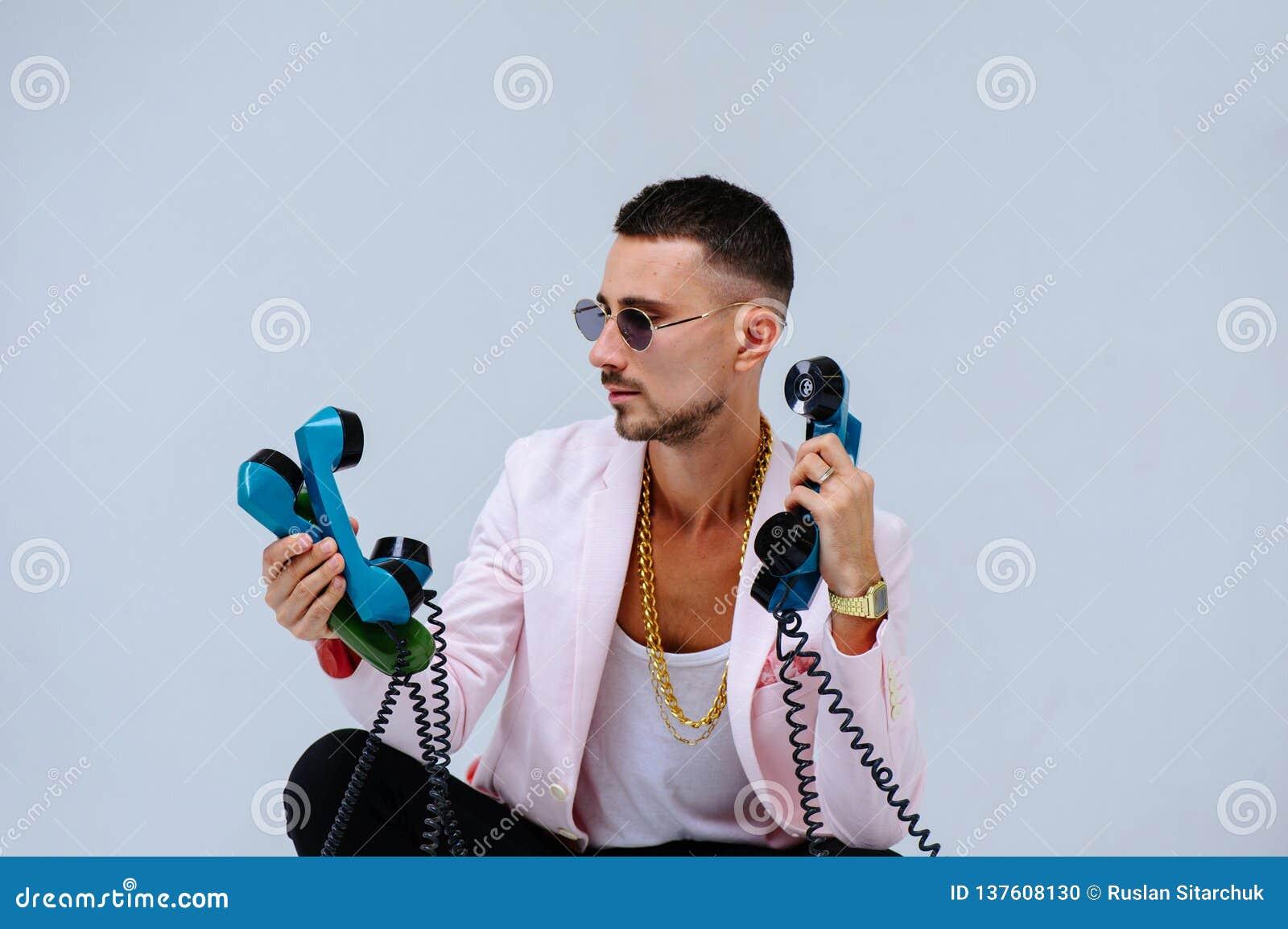 Uomo specializzato alla moda in un rivestimento rosa e nei pantaloni neri, con molti microtelefoni, l espressione dei gesti di em