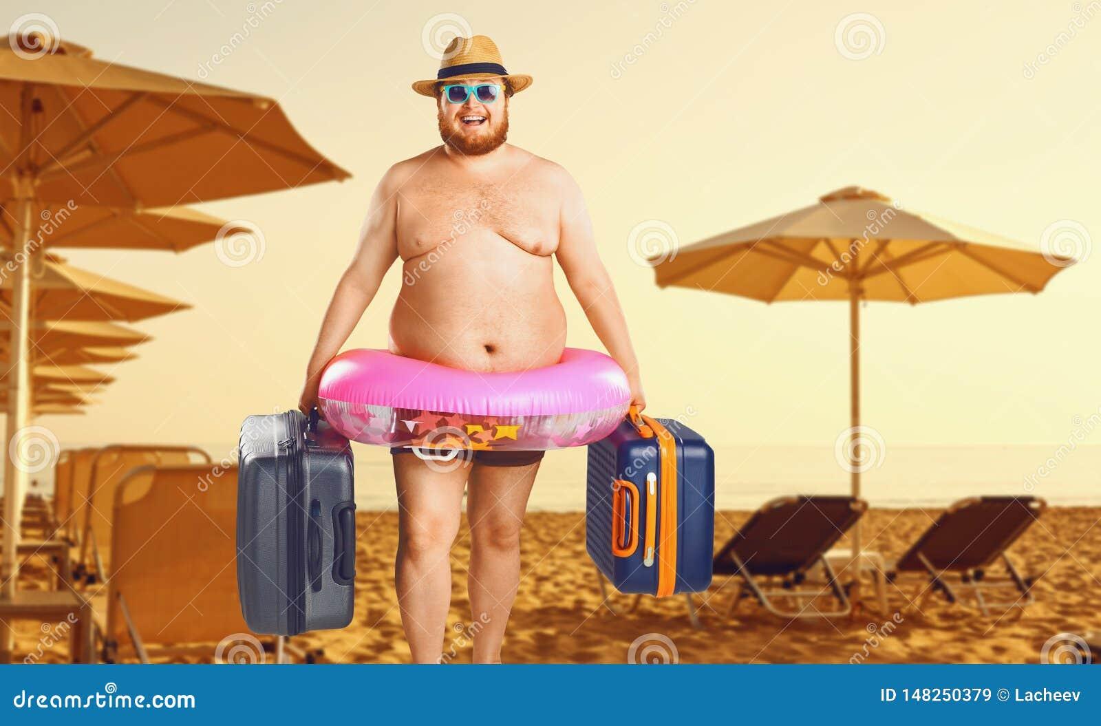Uomo spesso in un costume da bagno con una valigia e un anello di gomma contro lo sfondo di una spiaggia di estate