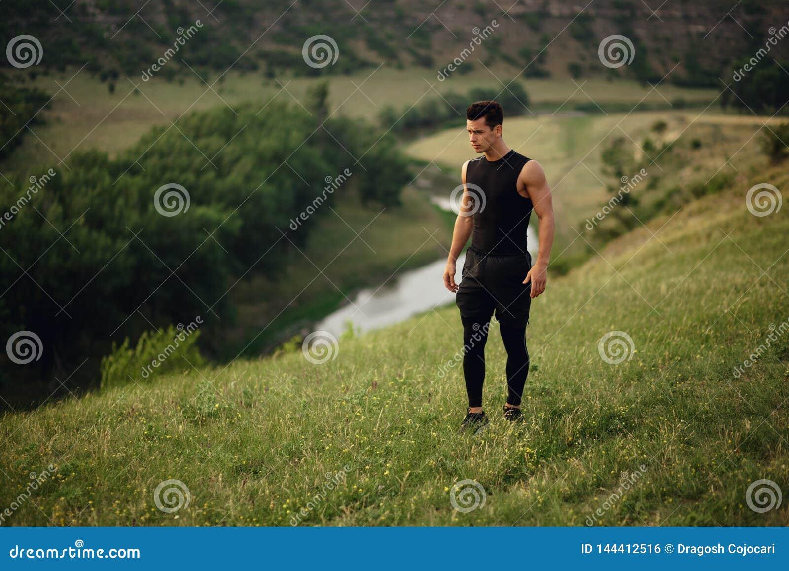 Uomo sportivo nell allenamento degli abiti sportivi fuori, isolato su un bello fondo del paesaggio