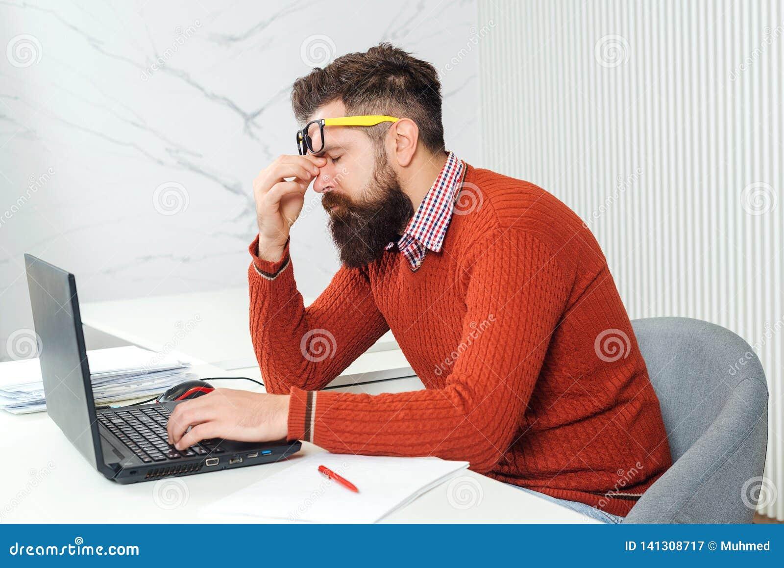 Uomo stanco con il computer portatile al posto di lavoro Uomo barbuto sovraccaricato all ufficio Uomo bello sollecitato di affari