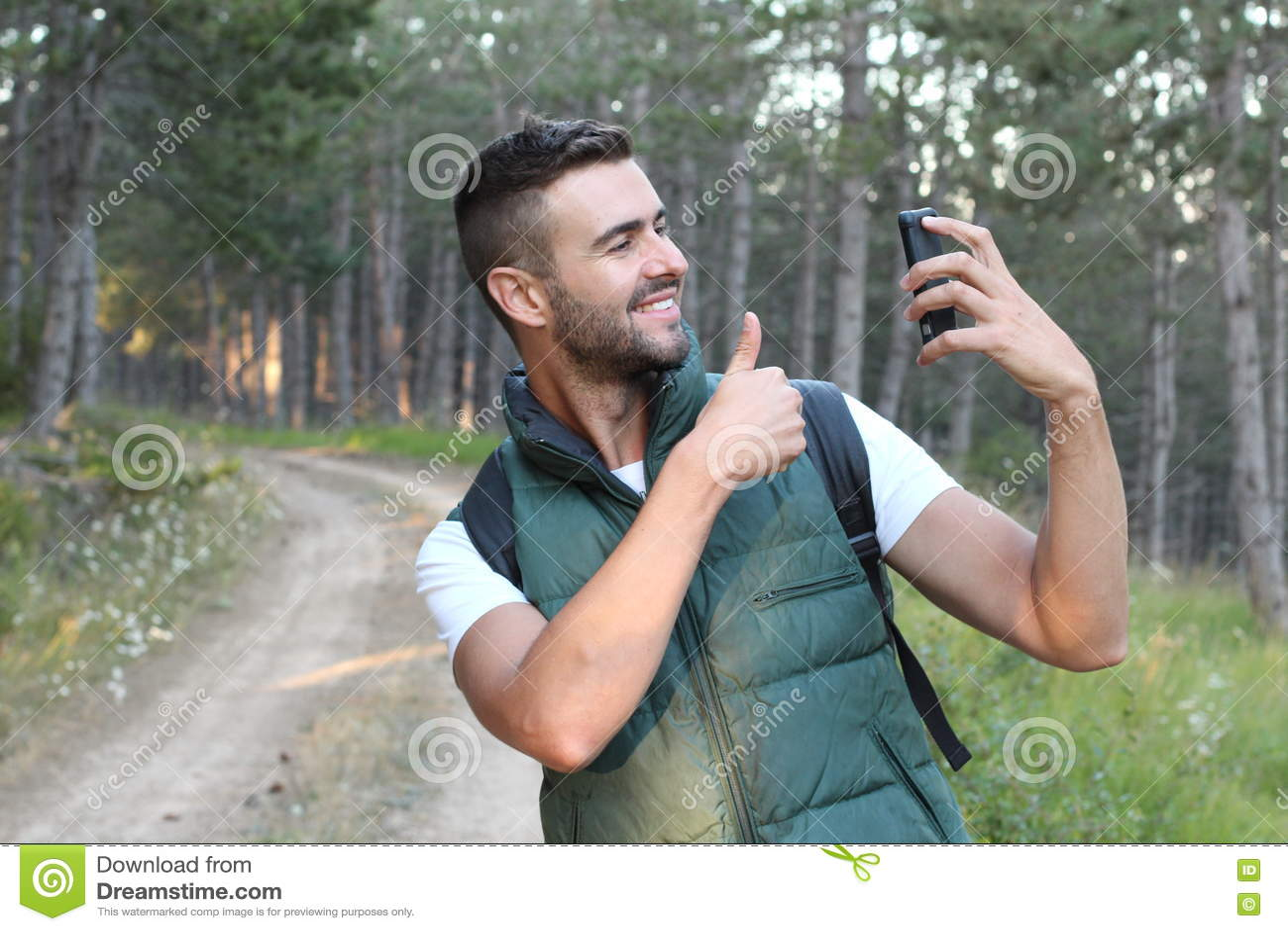 Uomo sveglio felice che fa la foto del selfie sullo smartphone e che mostra pollice su sopra il fondo della natura di legni o del