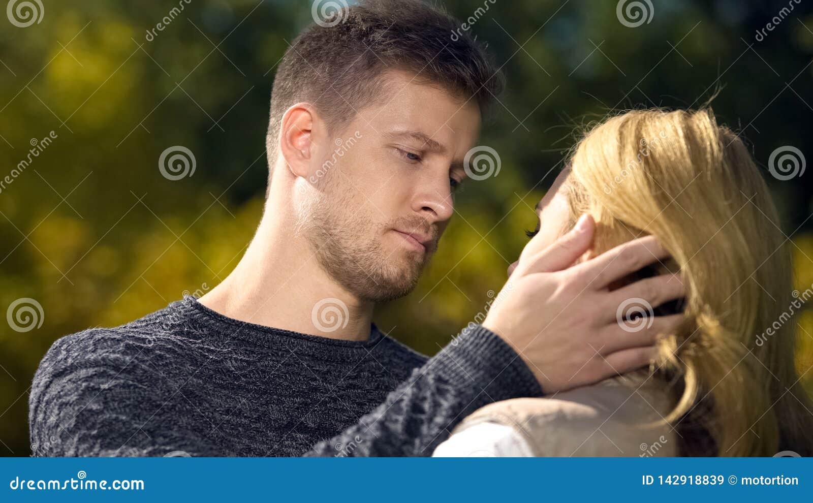 Uomo turbato che esamina donna e che tocca il suo fronte, mancanza di fondi, disoccupazione