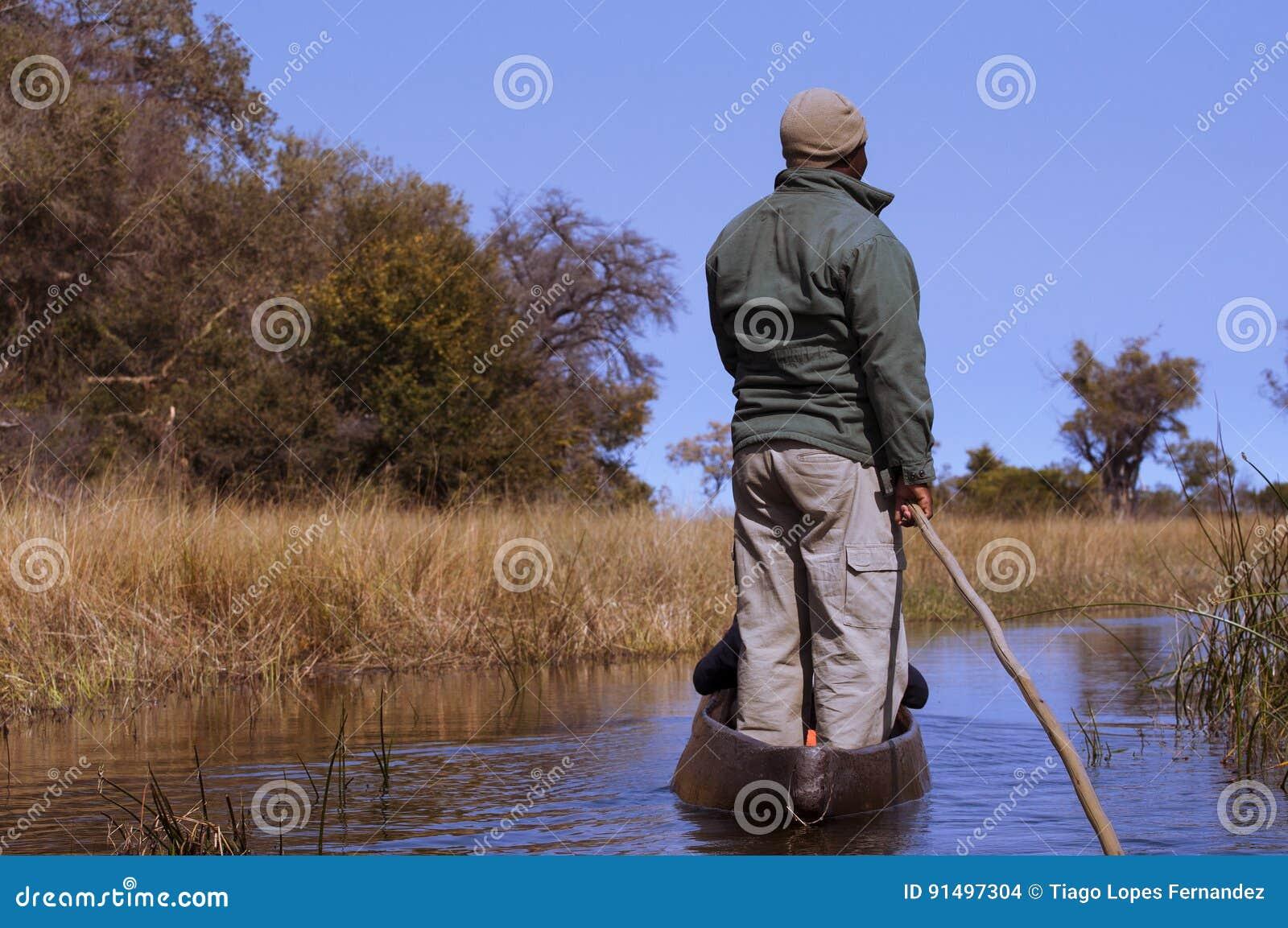 Uomo in una canoa nel delta di Okavango, Botswana di mokoro