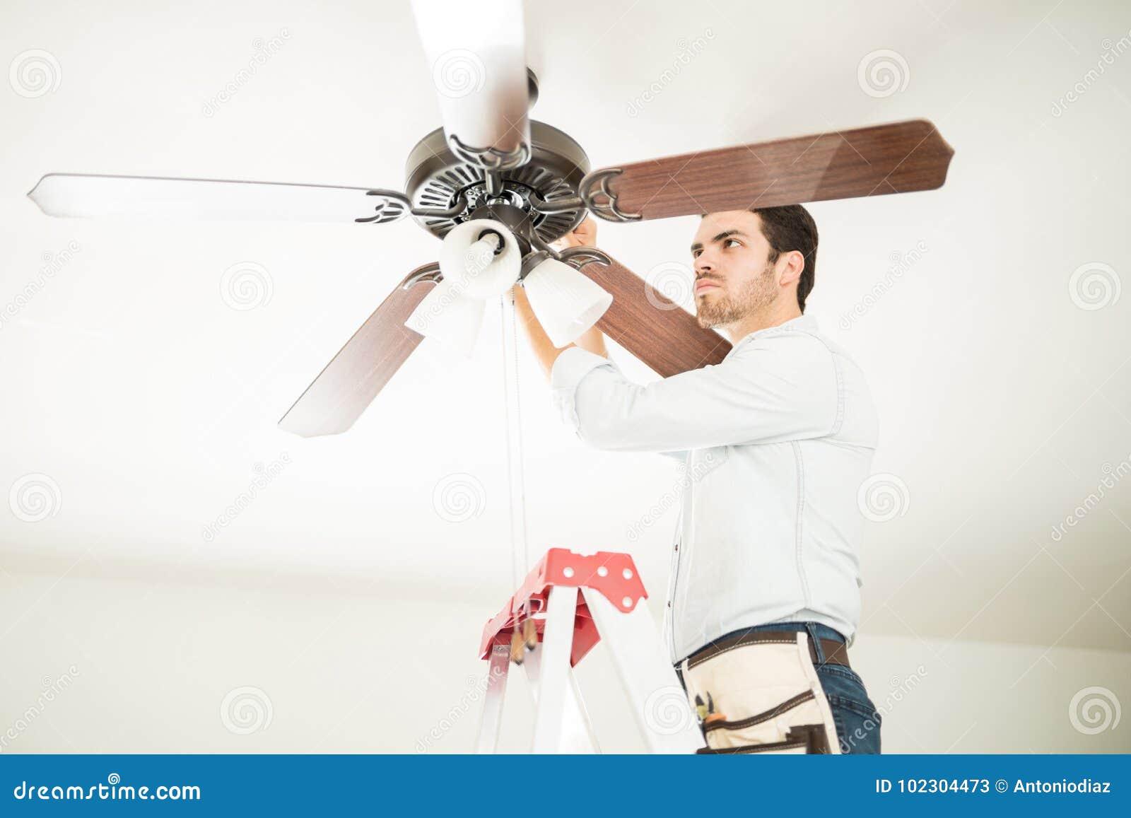 Uomo in ventilatore da soffitto della riparazione della scala