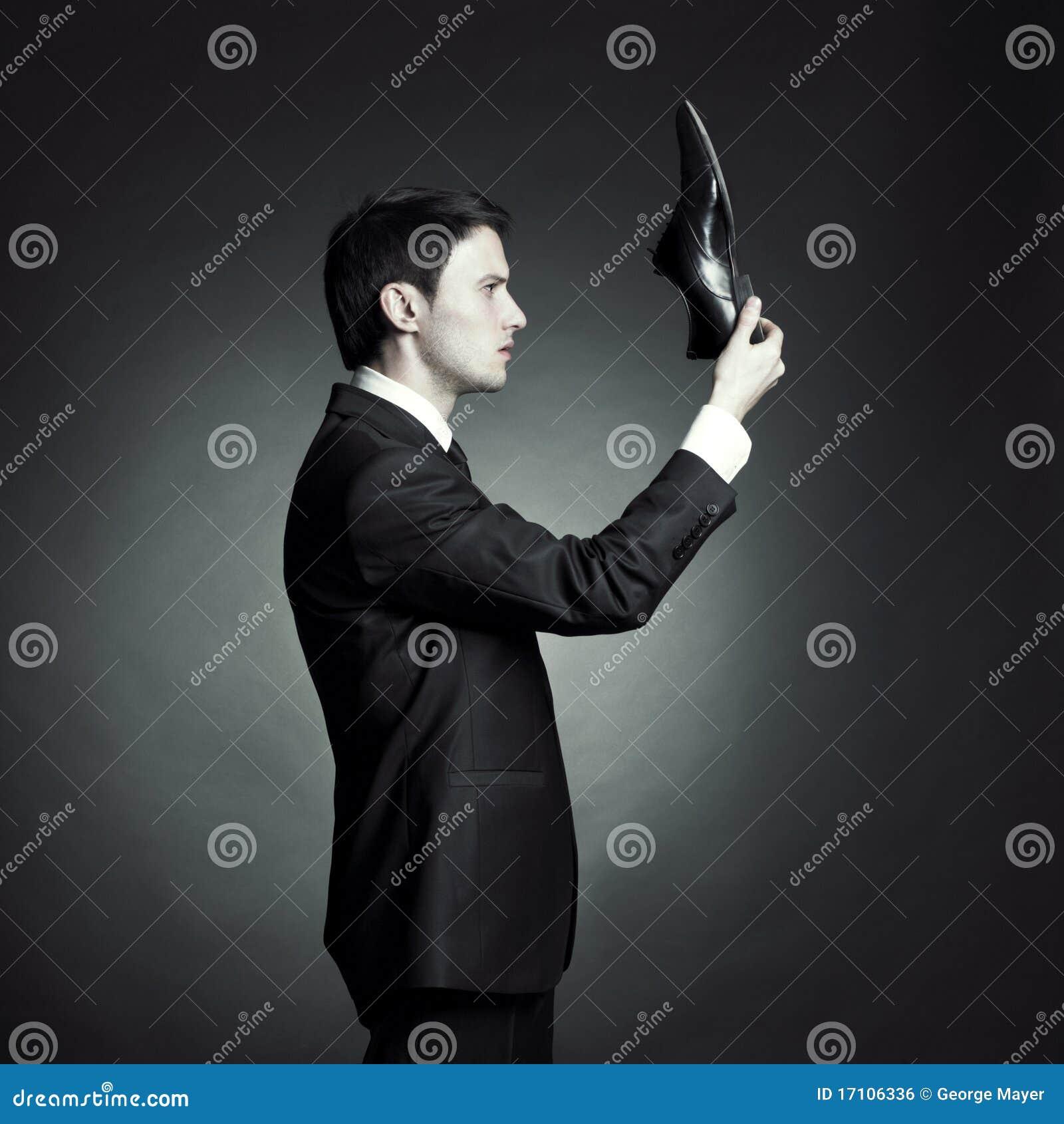 Uomo in vestito elegante e pattini a disposizione