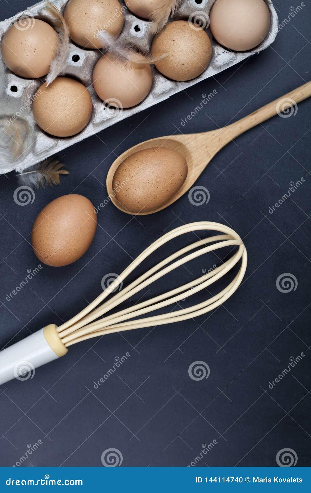 Uova, cucchiaio di legno, basette e piume Utensile della cucina per il dolce, la pasticceria o i biscotti sul fondo del piano di